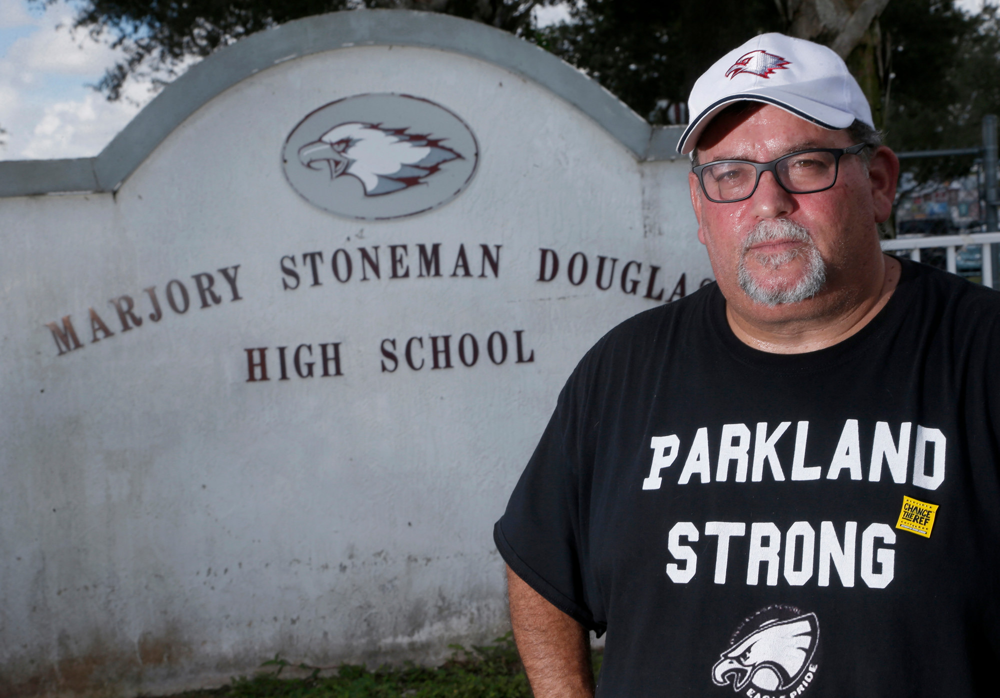 "Stephen Feuerman stands in front of the Marjory Stoneman Douglas High School sign in Parkland, Florida, recently. On 9/11, Stephen Feuerman saw the World Trade Center aflame through the window of his Empire State Building office. Feuerman had always seen himself as a New Yorker, but ""everything changed that day,"" he says."