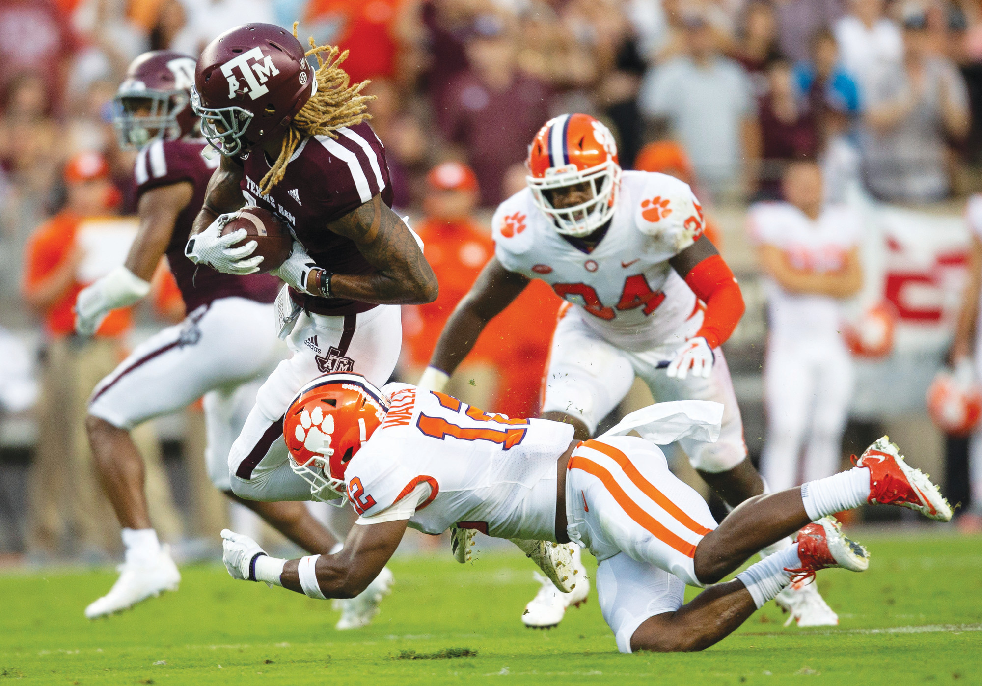 THE ASSOCIATED PRESSTexas A&M wide receiver Kendrick Rogers (13) breaks a tackle by Clemson defensive  back K'Von Wallace (12) in the Tigers' 28-26 win on Saturday in College Station, Texas. The Tigers have questions to answer about their dominant defense, which gave up 501 yards and three second-half touchdowns.