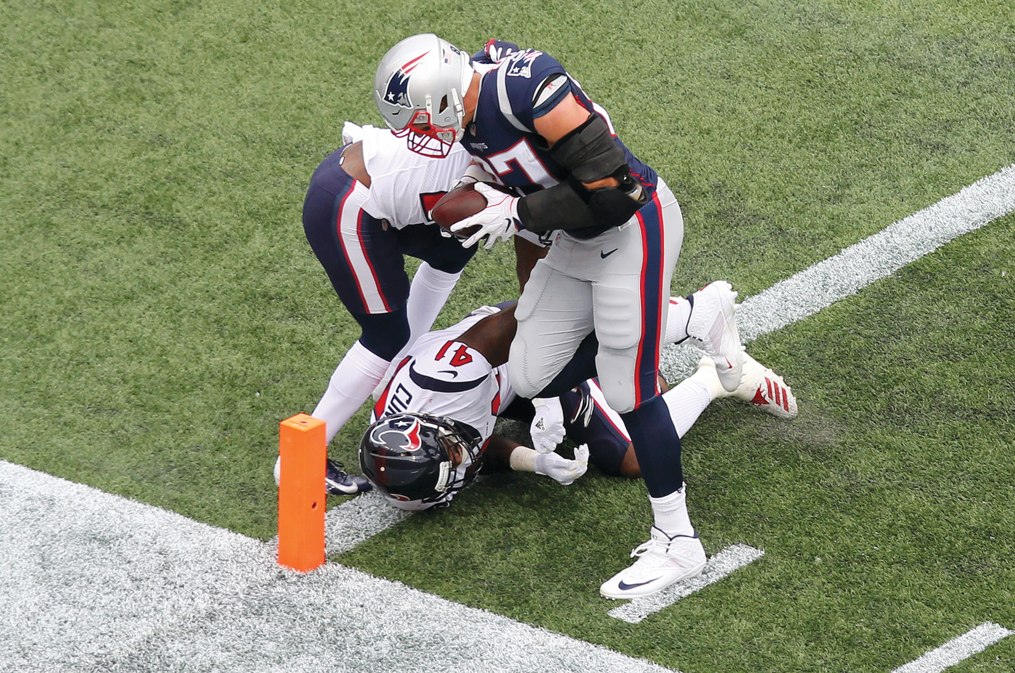 New England tight end Rob Gronkowski scores a touchdown past Houston Texans defensive Back Kareem Jackson, rear, and linebacker ZachCunningham (41) during the first half of their game Sunday in Foxborough, Massachusetts.
