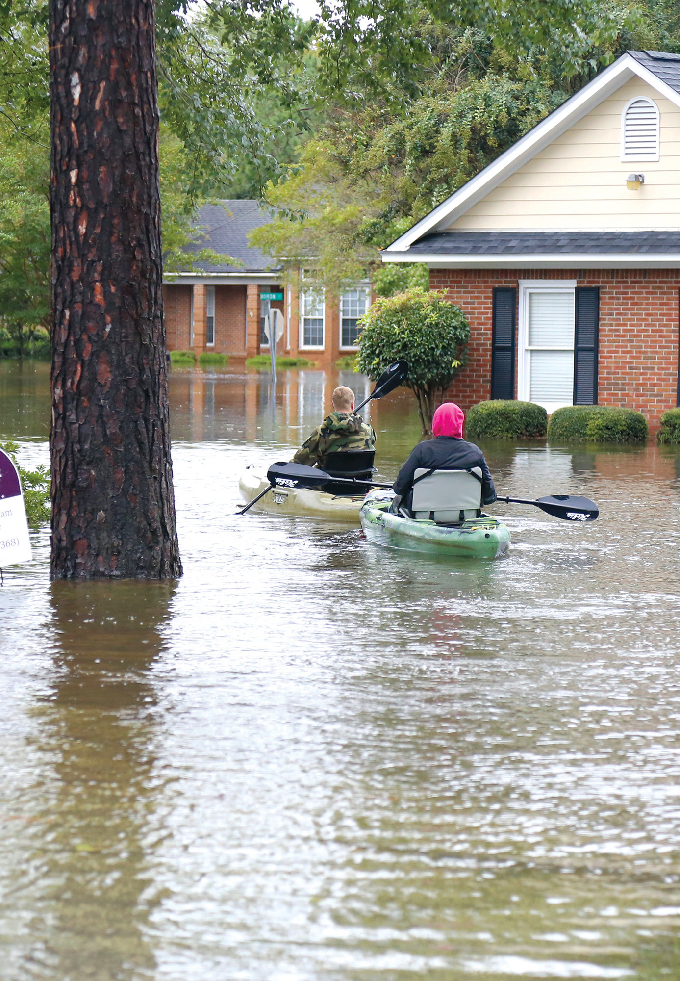 Residents of Golfair Court paddle through the neighborhood as waters from the 1,000-year flood remain after the indirect impact from Hurricane Joaquin.