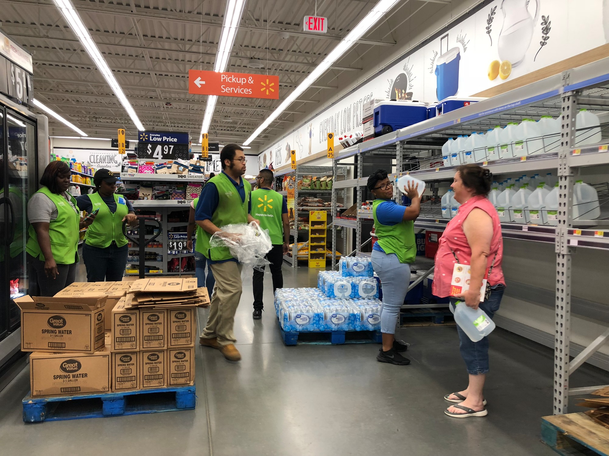 Employees at the Walmart Neighborhood Market on Pinewood Road restock bottled water Tuesday night as customers wait to stock up for Hurricane Florence.