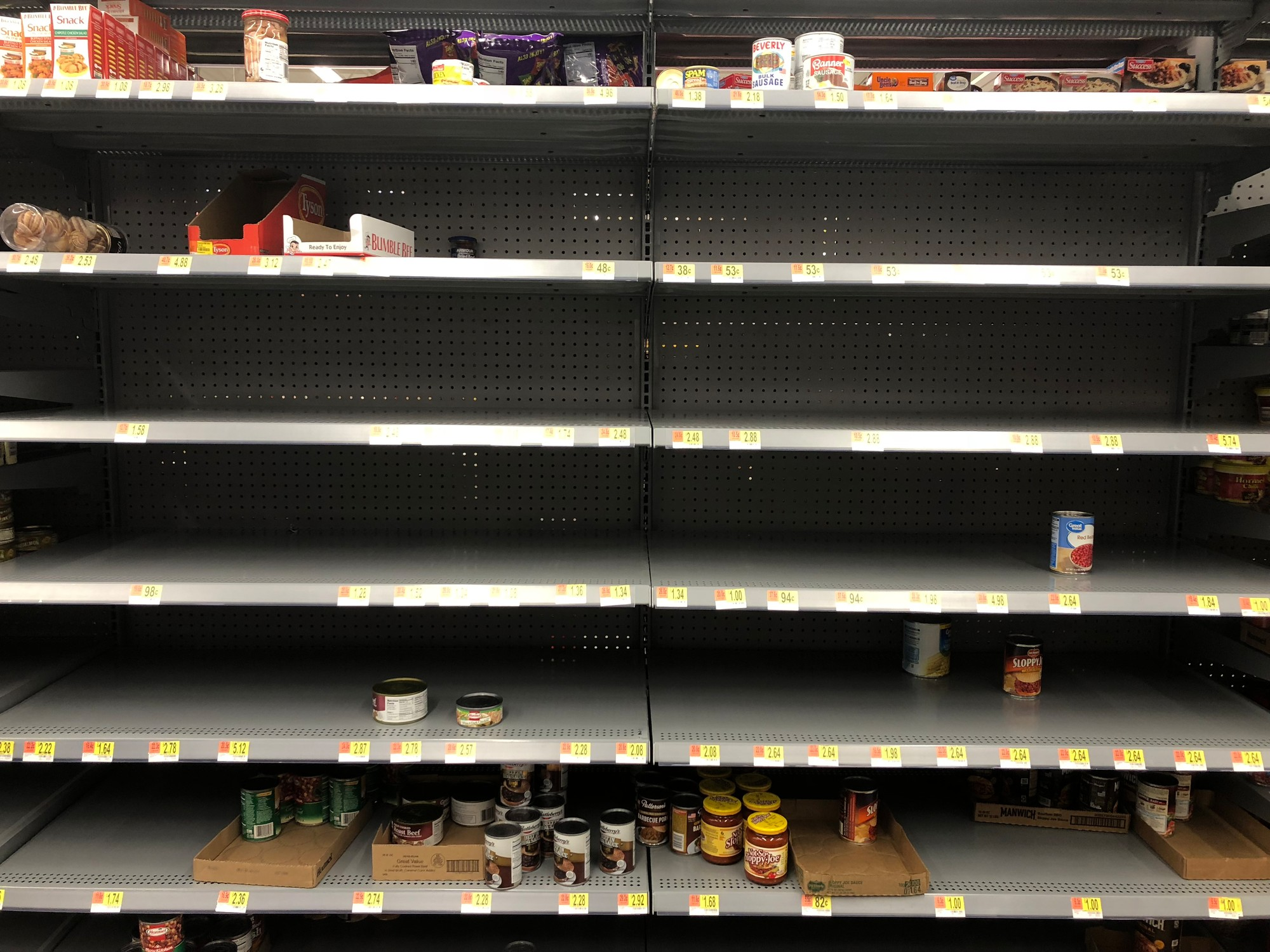Canned beans, vegetables and chili shelves are decimated Tuesday night at the Walmart Neighborhood Market on Pinewood Road as residents prepare for what is expected to be days without power due to Hurricane Florence.