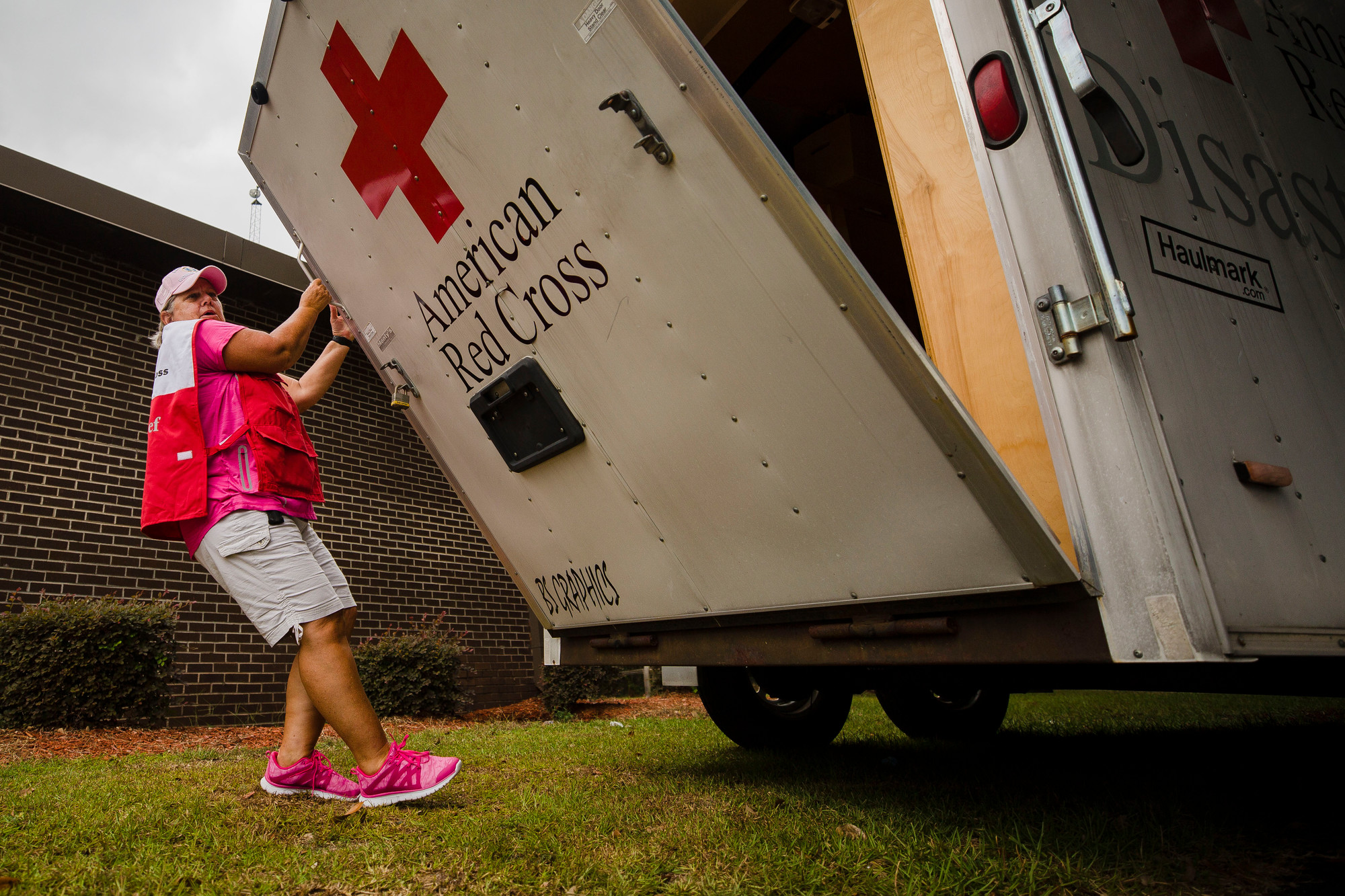 Patty Grimsley, a Red Cross volunteer, opens a trailer with cots and blankets outside of Mayewood Middle School on Thursday afternoon.