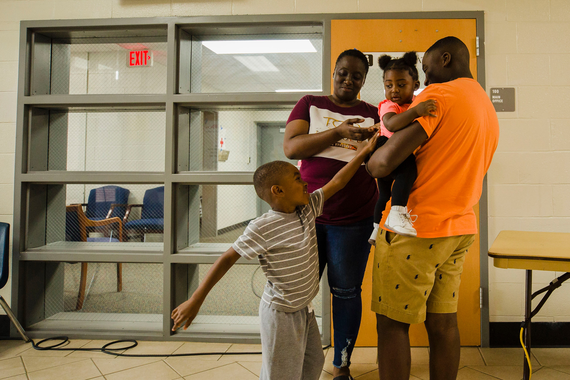 Surby Fullard, in maroon, and Chance Nero, in stripes, play around with Travis Johnson and Kelly Washington at the American Red Cross shelter at Mayewood Middle School on Thursday.