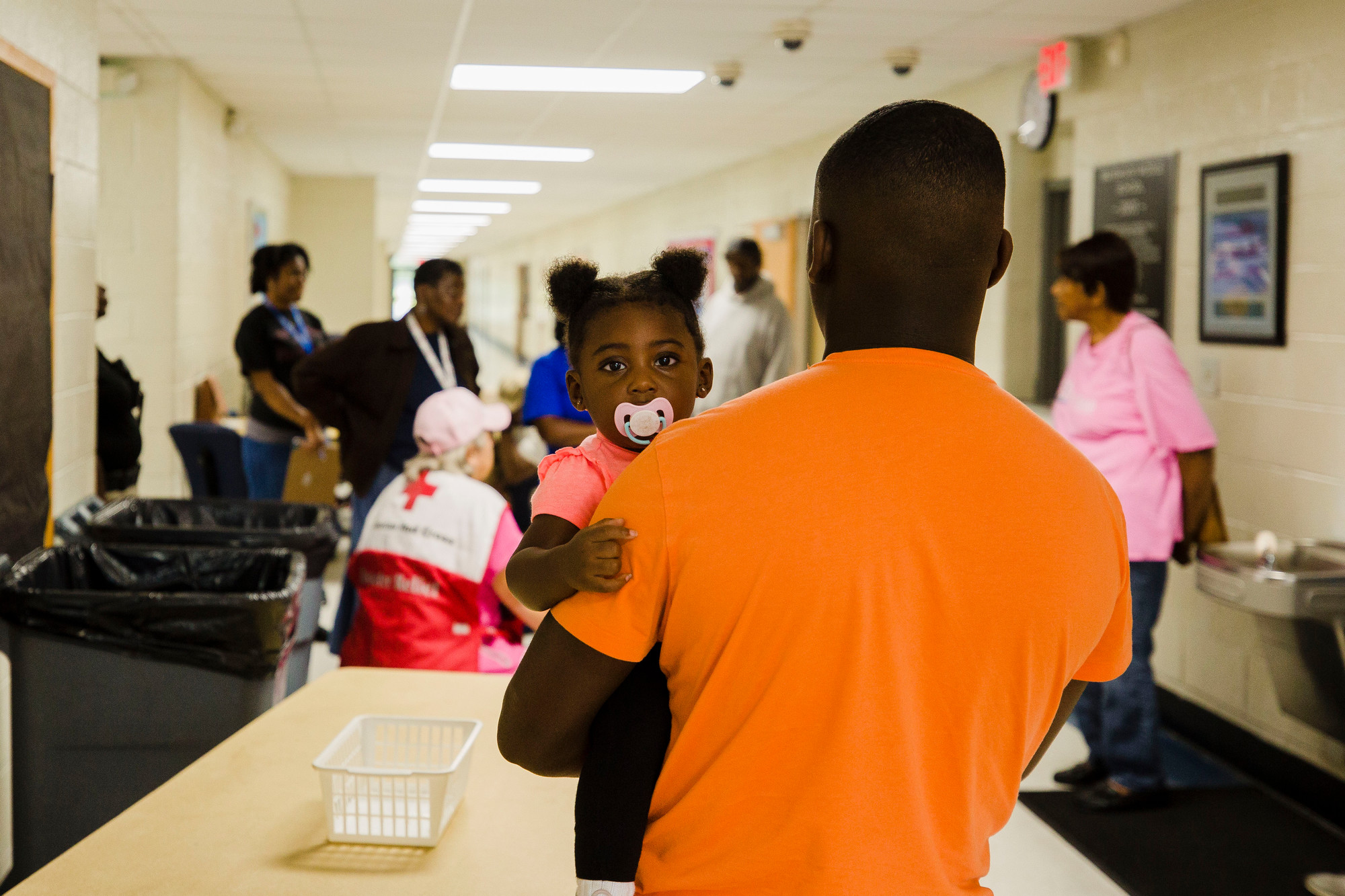 Kelly Washington looks at the camera while Travis Johnson holds her during a meeting of American Red Cross volunteers and DSS employees at Mayewood Middle School Thursday.