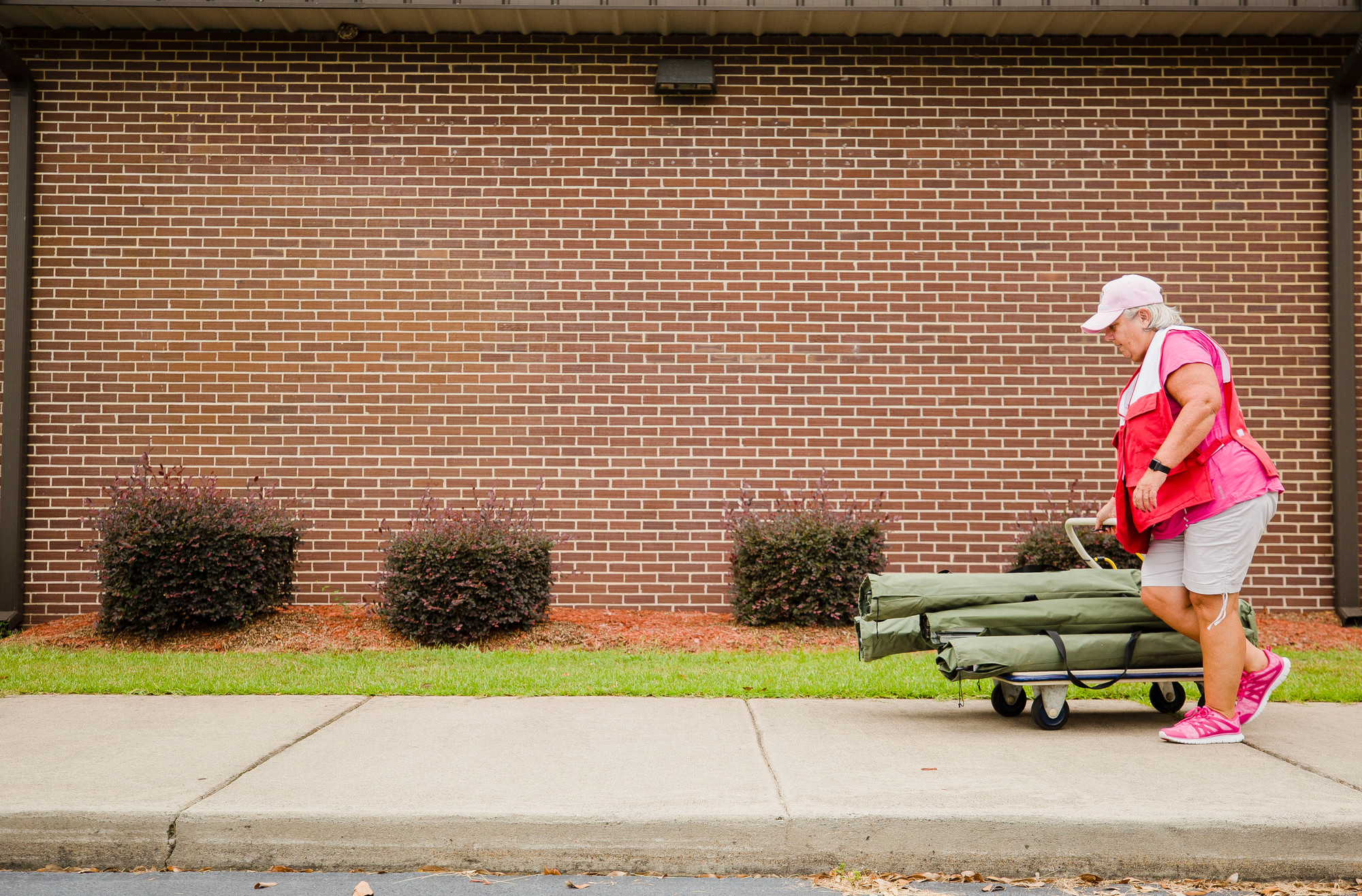 Patty Grimsley, a Red Cross volunteer, wheels in cots to the Mayewood Middle School American Red Cross shelter on Thursday.