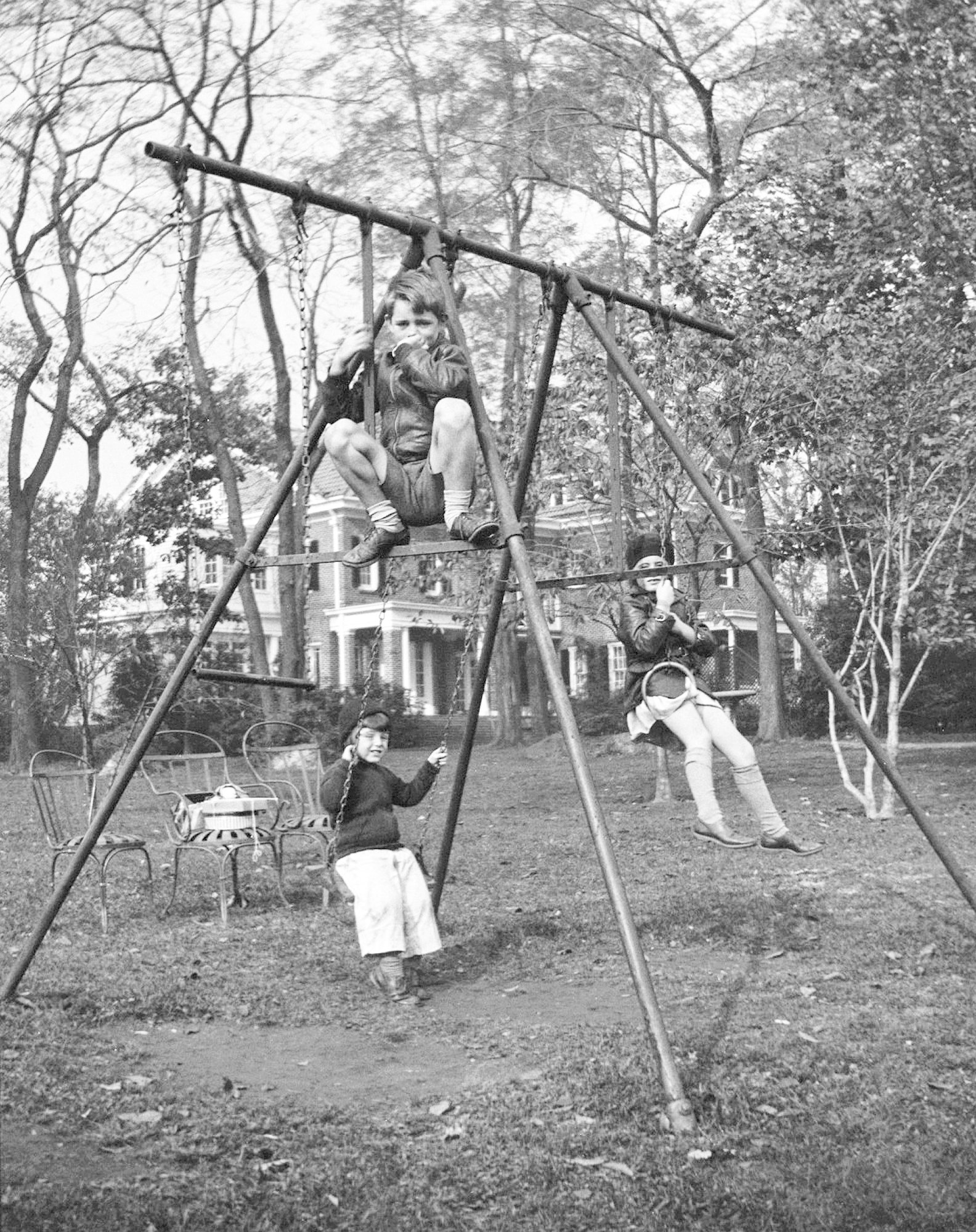 In this October 1934 photo, Robert F. Kennedy, top front, Edward M. Kennedy, left rear, and Jean Kennedy, right rear, play on a swing set in Bronxville, New York.