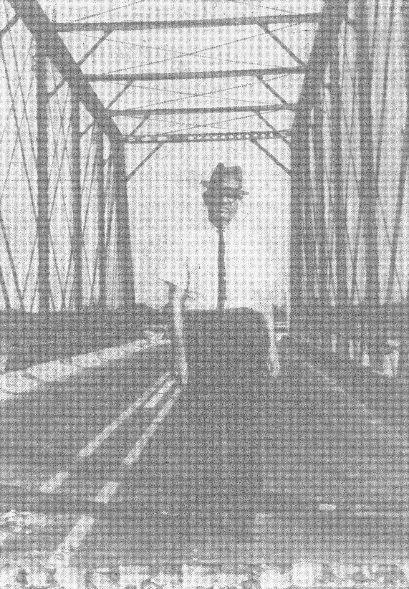 B. K. Mills, roadmaster for the Atlantic Coast Line Railroad, waits in 1964 for the Pinewood Road Bridge to be removed from its moorings so he can take it away. The steel bridge, property of the railroad, will be lowered onto rail cars and hauled to a repair shop for rebuilding and relocation.