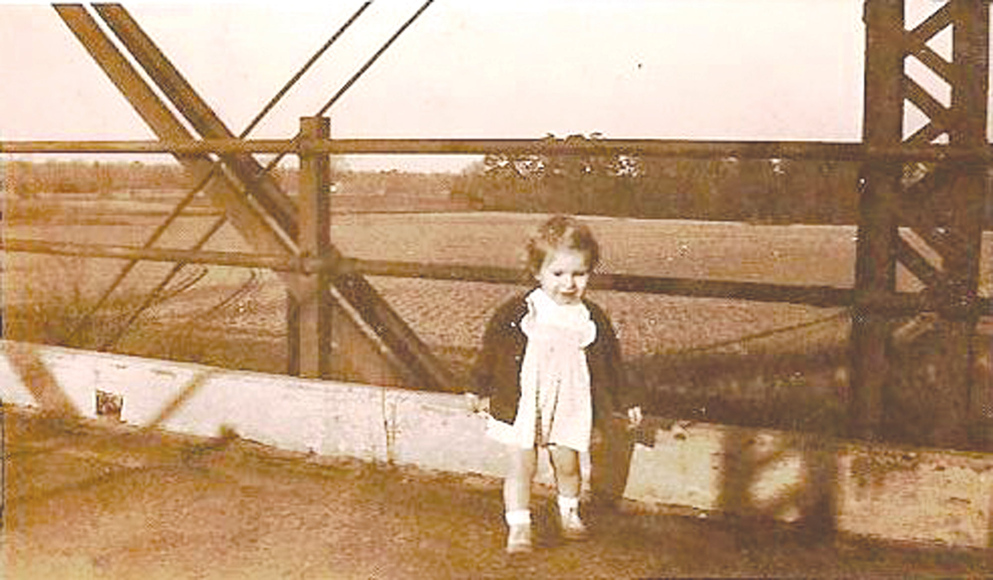 A child stands on the Pinewood Road bridge.