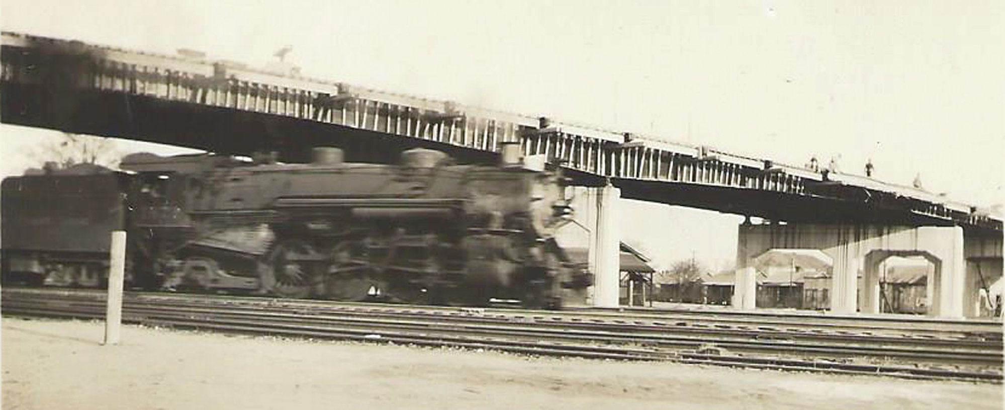 A train passes underneath the Manning Avenue bridge over the railroad yard.