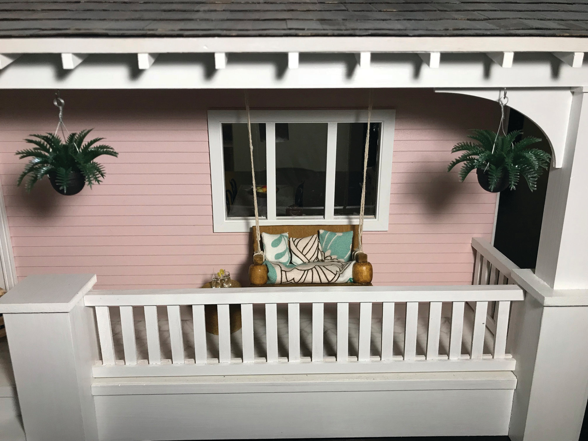 Amy Dorman's miniature pink bungalow has a porch swing, farmhouse table and even its own dollhouse in the craft area.