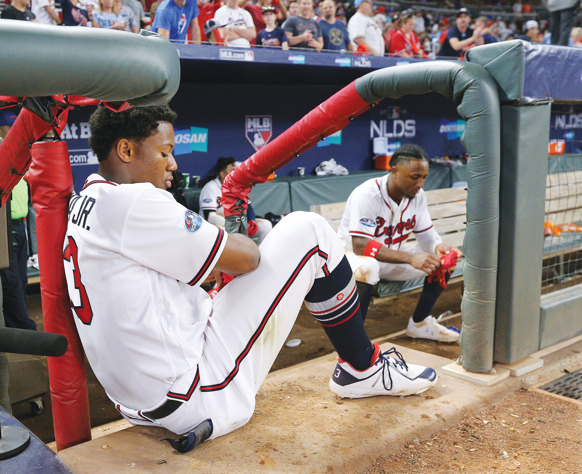 Atlanta's Ronald Acuna Jr., left, and Ozzie Albies sit in the dugout while the Los Angeles Dodgers celebrate their series-clinching Game 4 victory in their National League Division Series on Monday in Atlanta.