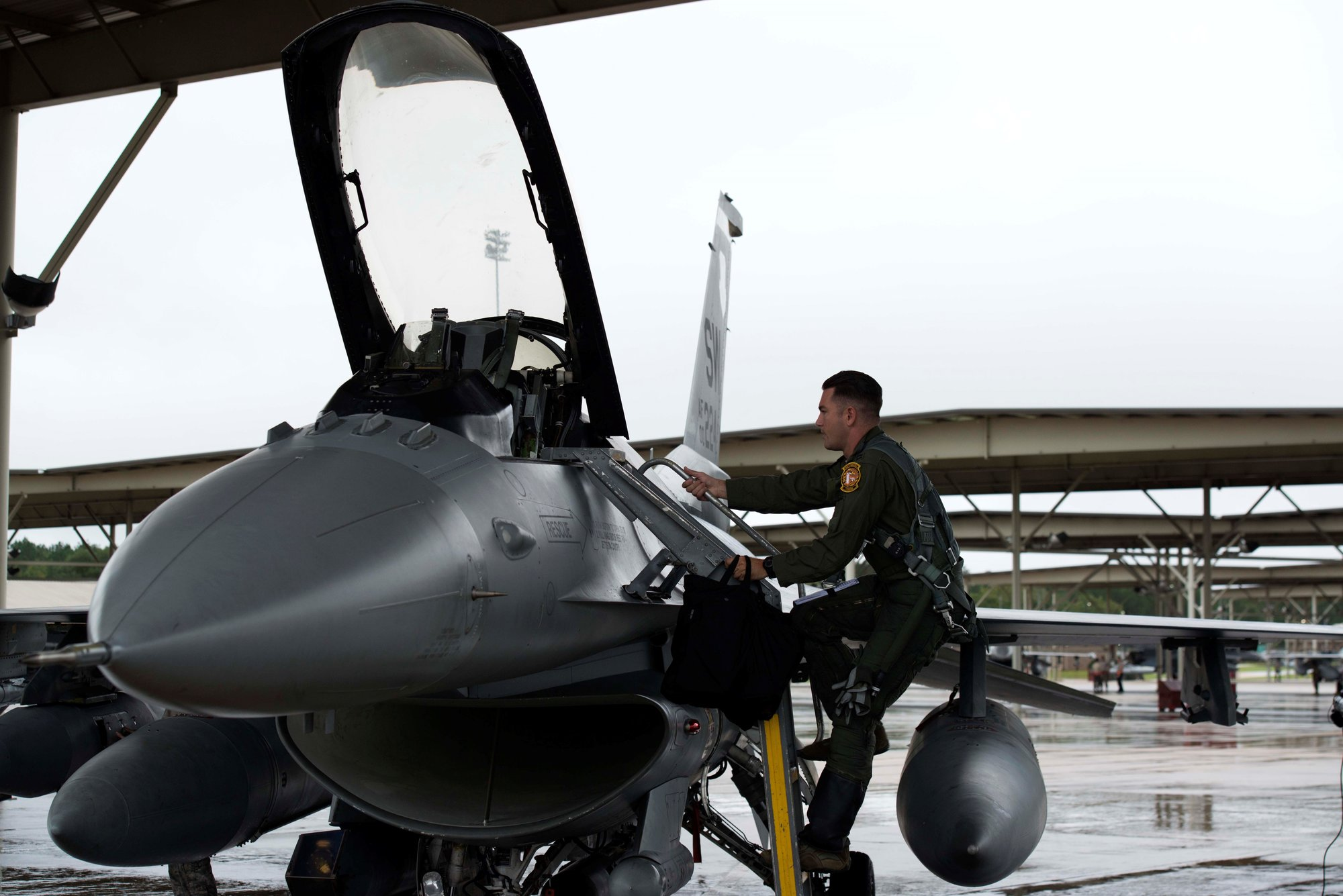 A U.S. Air Force pilot assigned to the 79th Fighter Squadron climbs into an F-16 Fighting Falcon at Shaw Air Force Base on Wednesday, Oct. 10. Pilots from the 55th, 77th and 79th FSs evacuated Shaw's jets to avoid possible damage from Hurricane Michael.