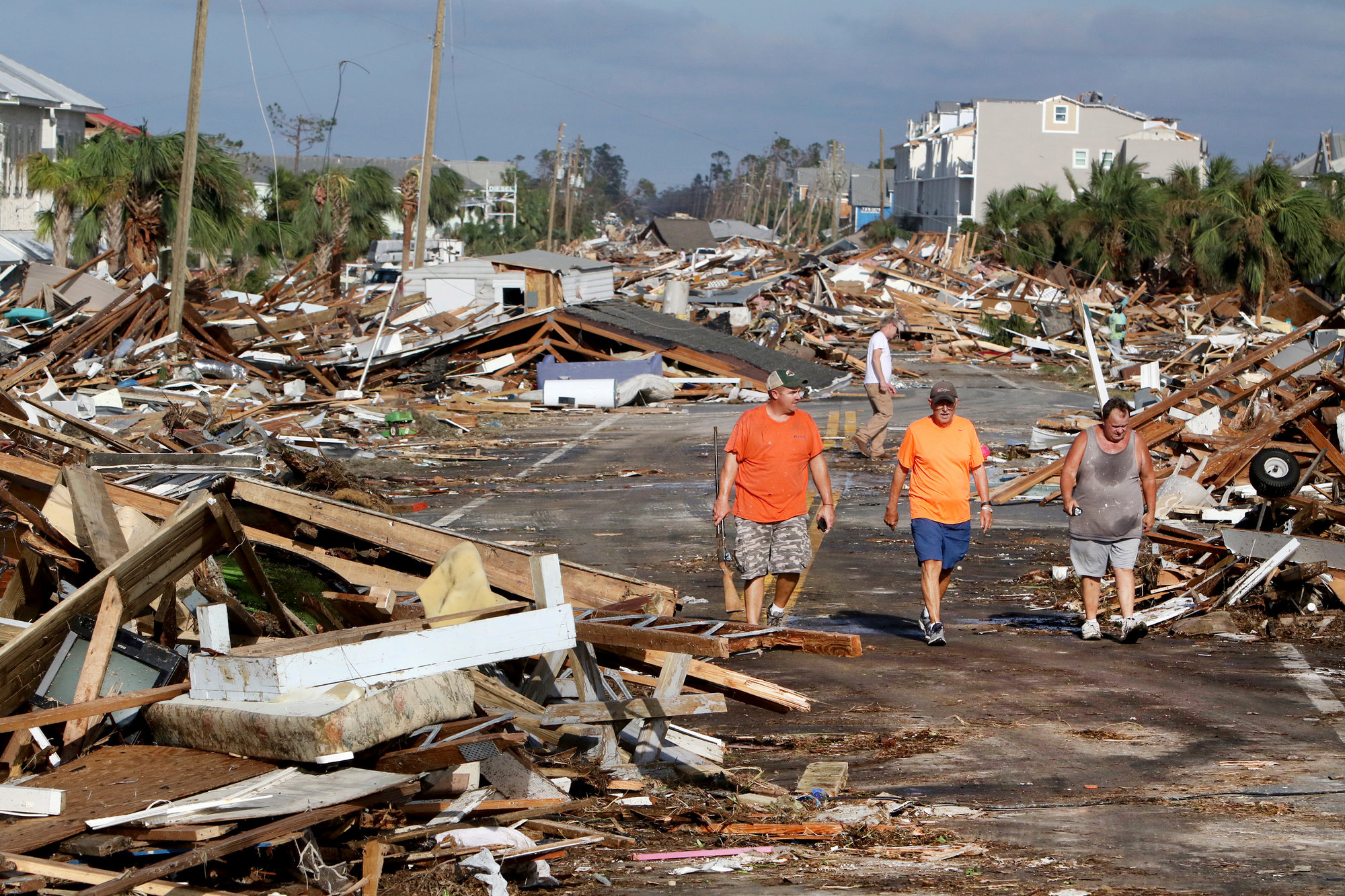 From left, Lee Cathey, 37; Al Cathey, 71; and Charles Smith, 56, survey damage in Mexico Beach, Florida, population 1,200, which lay devastated on Thursday after Hurricane Michael made landfall Wednesday in the Florida Panhandle.