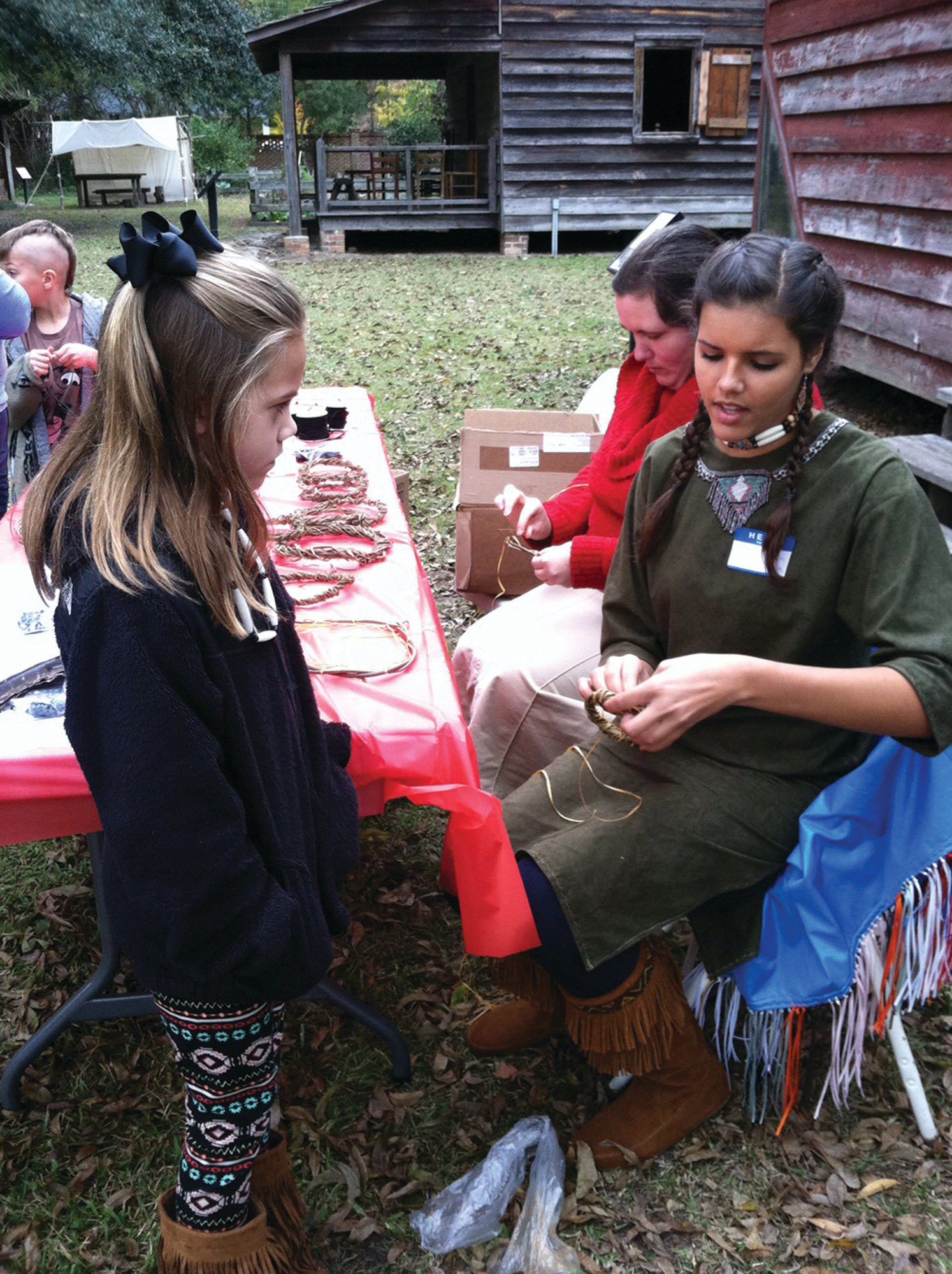 Karli Hudson helps a child make a dream catcher at a previous tribe event.