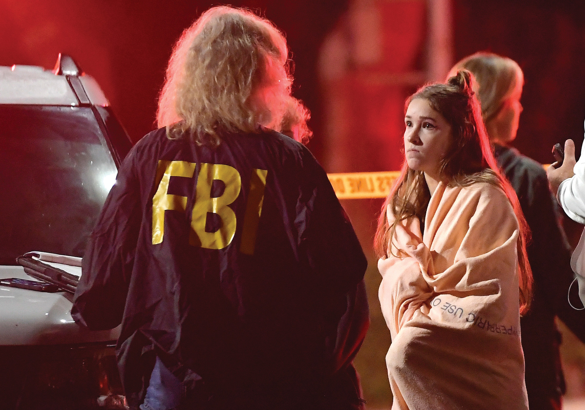 "THE ASSOCIATED PRESSAn FBI agent talks to a potential witness as they stand near the scene Thursday in Thousand Oaks, California, where a gunman opened fire Wednesday inside a country dance bar crowded with hundreds of people on ""college night."""