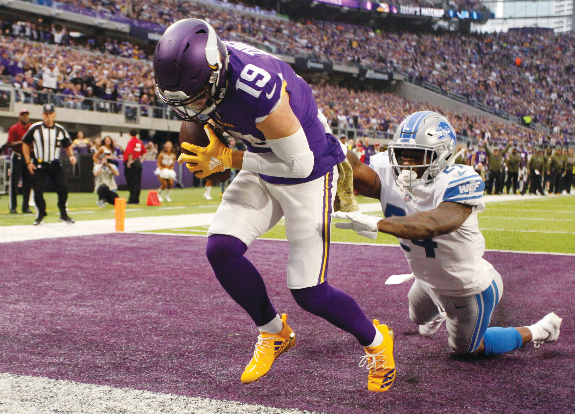 FILE - In this Nov. 4, 2018, file photo, Minnesota Vikings wide receiver Adam Thielen (19) catches a 2-yard touchdown pass ahead of Detroit Lions cornerback Nevin Lawson, right, during the first half of an NFL football game in Minneapolis. Thielen became the first player to have eight 100-yard receiving games to start a season, tying Calvin Johnson for the longest streak of such games. The former undrafted wide receiver has 78 catches for the Vikings. He's on pace to challenge Marvin Harrison's