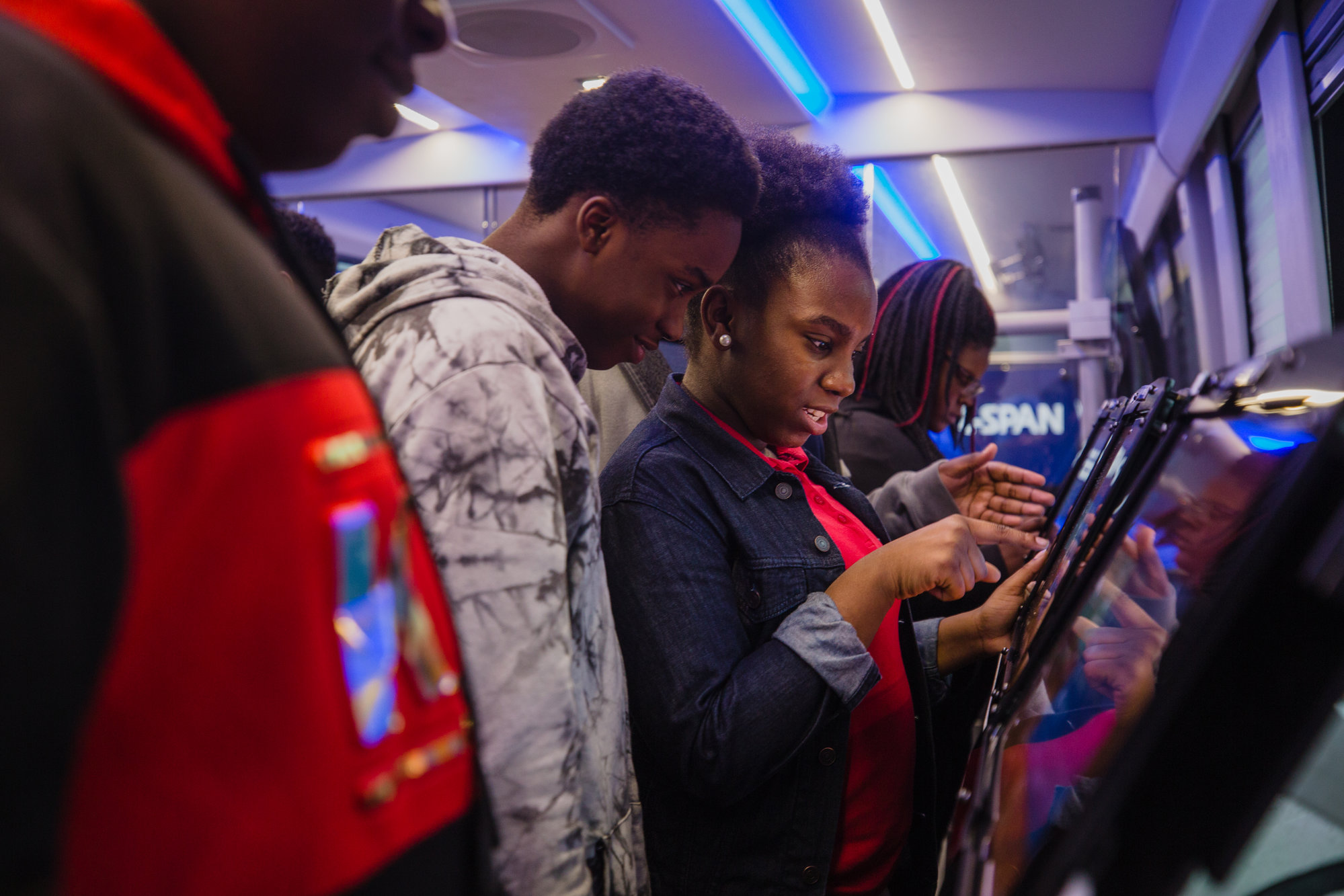 Eighth-graders from R.E. Davis check out touch screens filled with quizzes, videos and other educational information on board the C-SPAN Bus.