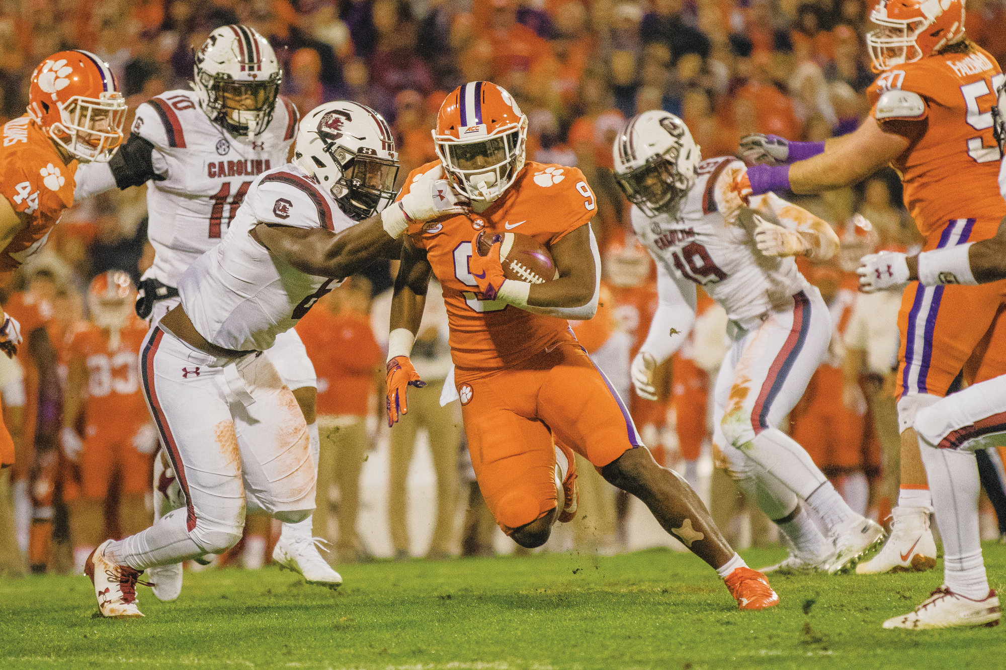 Clemson running back Travis Etienne (9) runs with the ball as South Carolina linebacker T.J. Brunson tries to get a hold of him during the Tigers' 56-35 victory on Saturday in Clemson. The Tigers will take on Pittsburgh in the Atlantic Coast Conference championship game this Saturday in Charlotte.