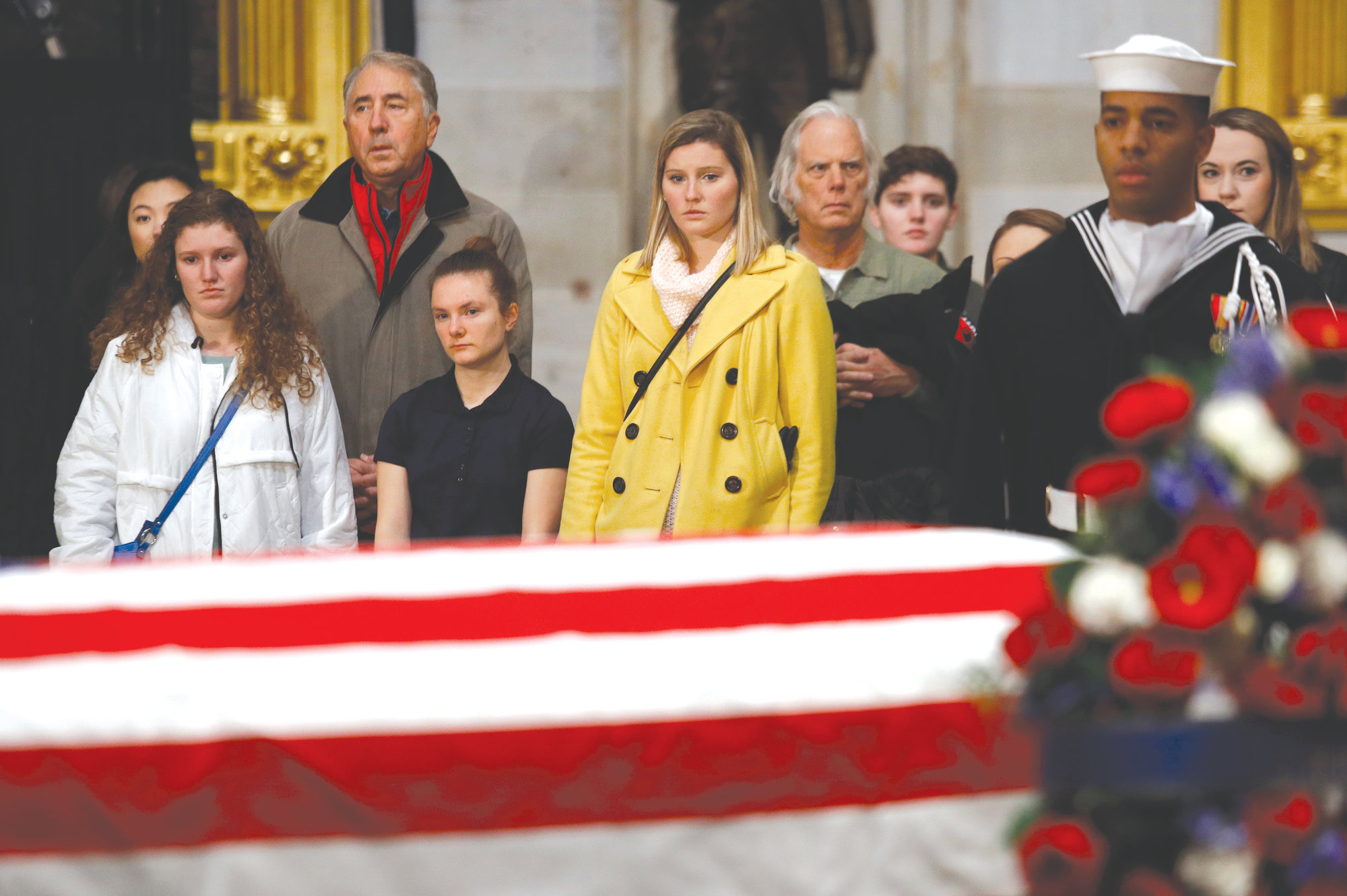 Visitors file past the flag-draped casket of former President George H.W. Bush as he lies in state in the Capitol Rotunda in   Washington on Tuesday.