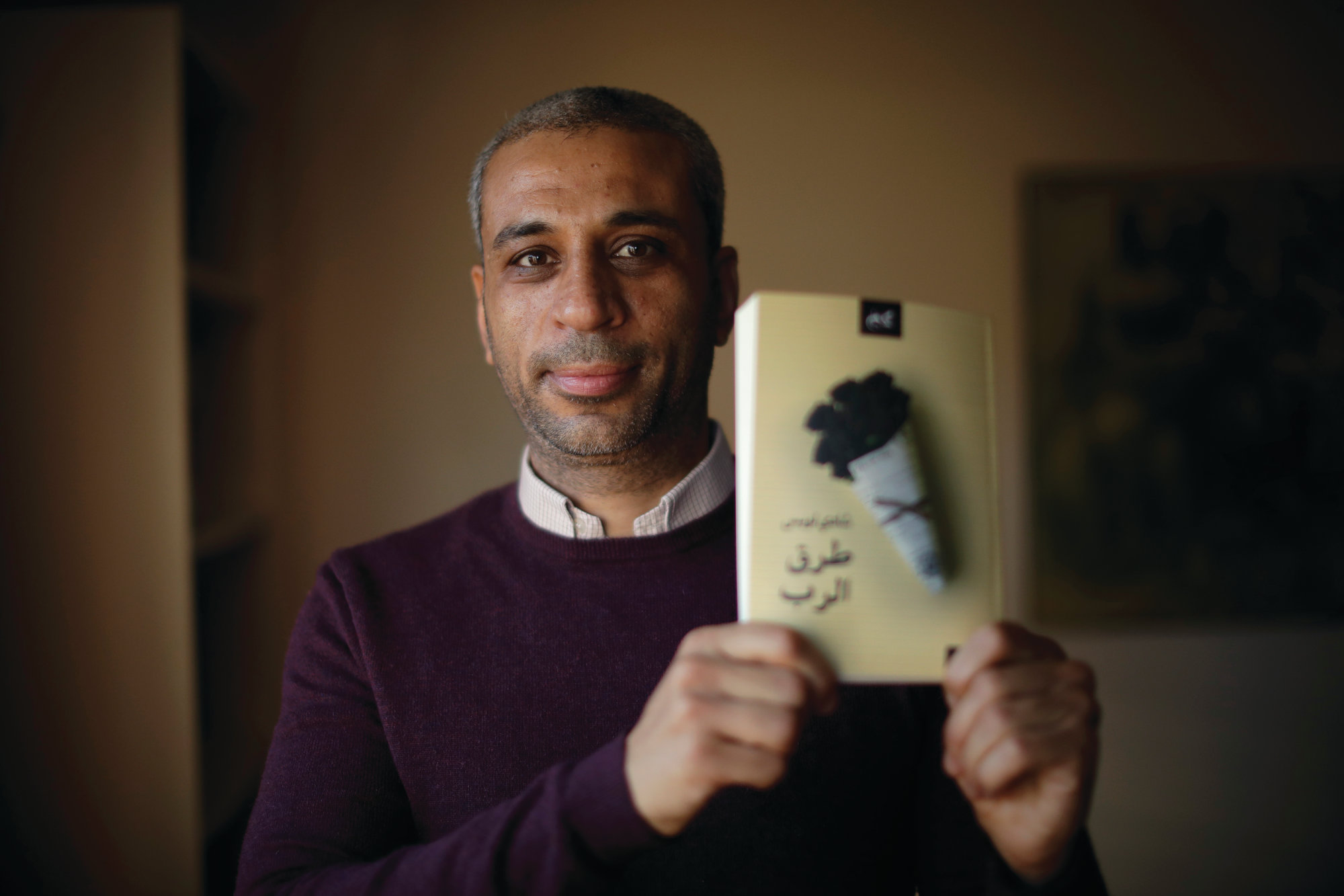 "THE ASSOCIATED PRESS   Journalist and author Shady Lewis Botros poses with a copy of his book, ""Ways of the Lord."""
