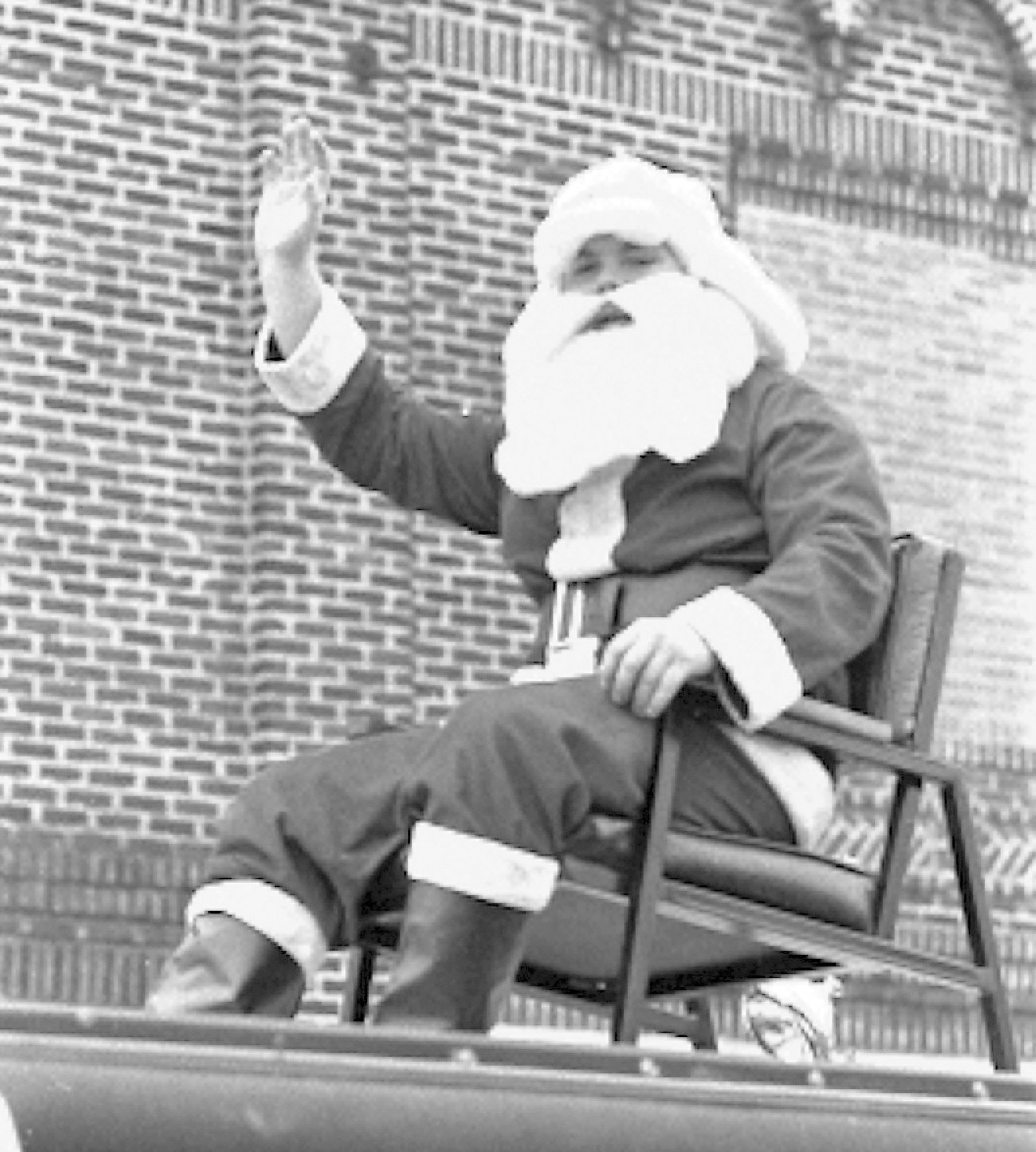 Santa waves to the crowd from a lawn chair during the Christmas parade in 1971.