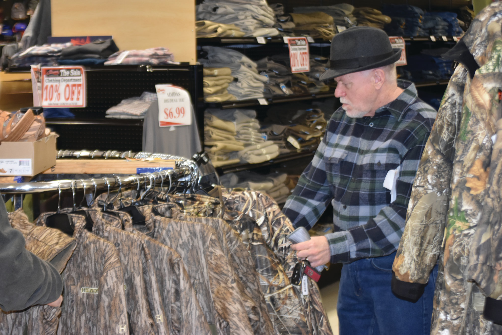 BRUCE MILLS / THE SUMTER ITEM  A customer looks through a rack of camouflage items that were priced 40 percent off on Thursday at Simpson Hardware & Sports.