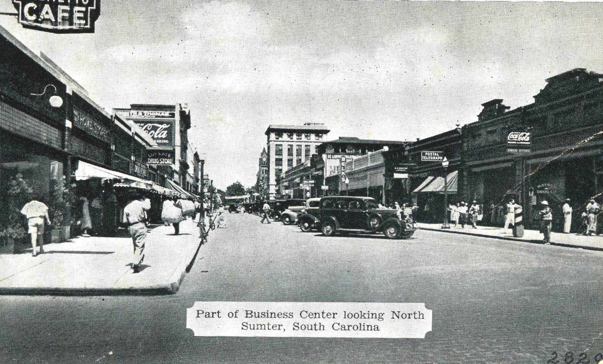 The popular Palmetto Cafe was originally located at the corner of South Main and Dugan streets, near where Sumter Cut-Rate Drug Store now stands. Part of its sign can be seen at top left.