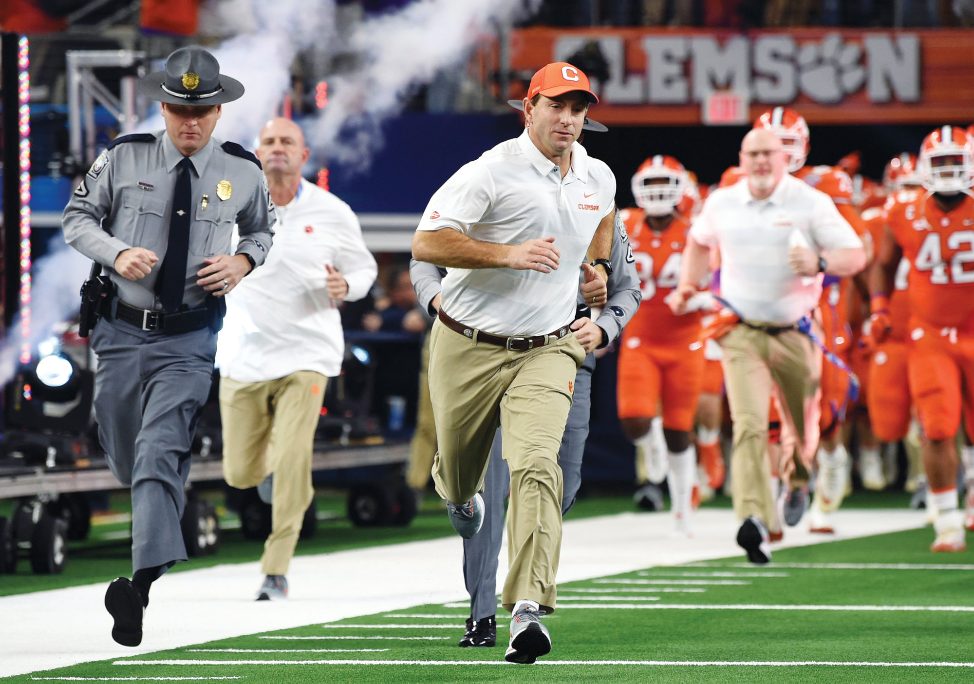 Clemson head coach Dabo Swinney jogs onto the field for the first half of the Cotton Bowl playoff semifinal game against Notre Dame on Saturday in Arlington, Texas. The Tigers earned a spot in Monday's national championship game against Alabama with a 30-3 victory over the Fighting Irish.
