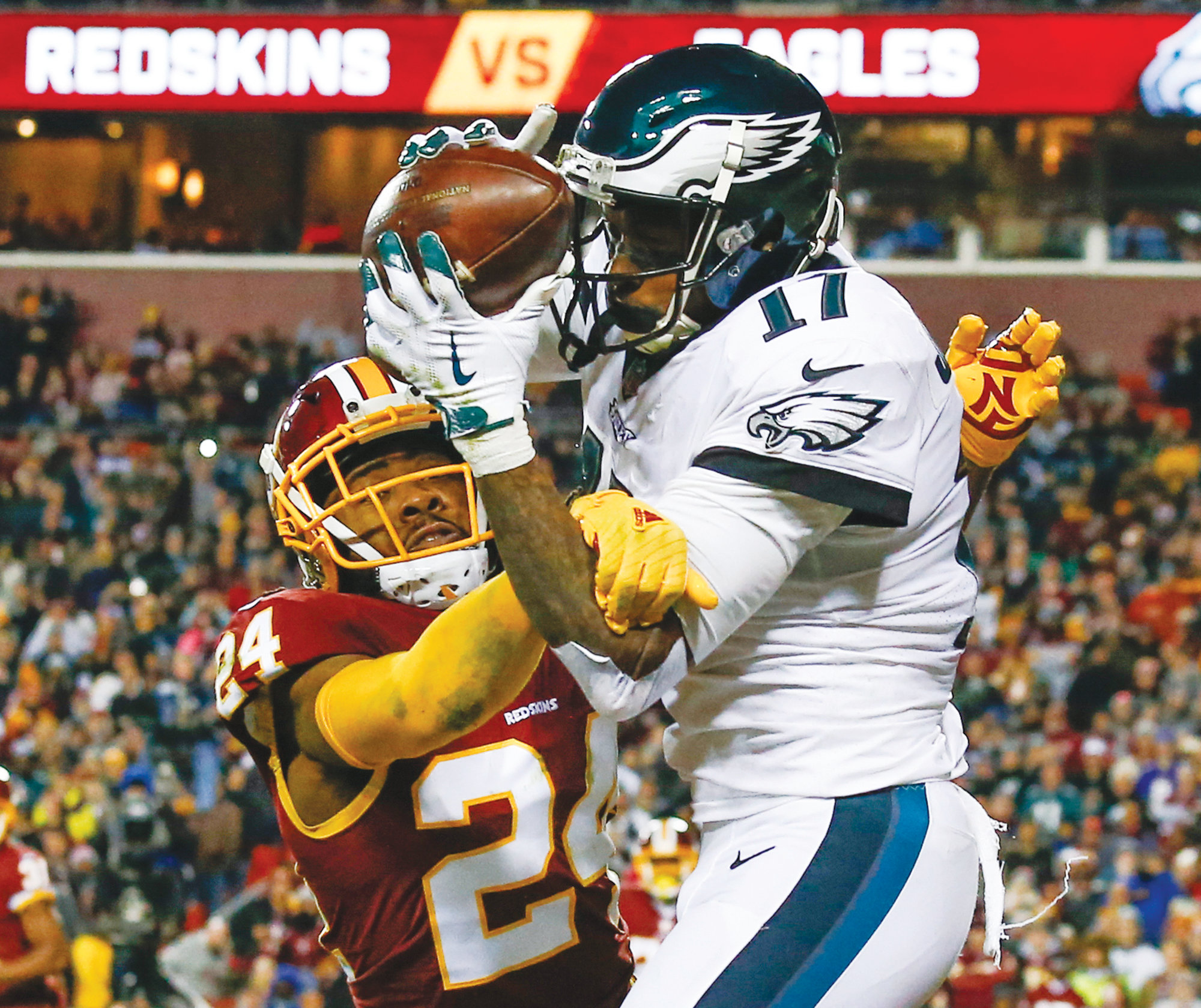 Philadelphia Eagles wide receiver Alshon Jeffery (17) pulls in a touchdown pass under pressure from Washington Redskins cornerback Josh Norman (24) during the first half of the NFL football game between the Washington Redskins and the Philadelphia Eagles, Sunday, Dec. 30, 2018 in Landover, Md. (AP Photo/Alex Brandon)