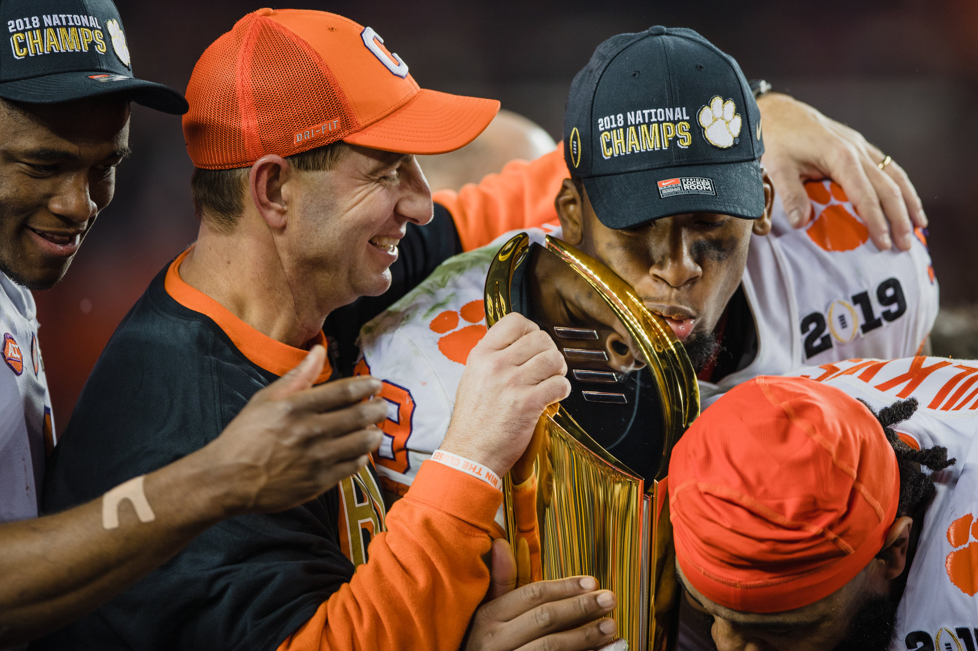 Clemson quarterback Dabo Swinney smiles on as defensive end Clelin Ferrell shows affection to the trophy after the Tigers routed Alabama 44-16 on Monday, Jan. 7 at Levi's Stadium in Santa Clara, California, to win the 2019 CFP National Championship.
