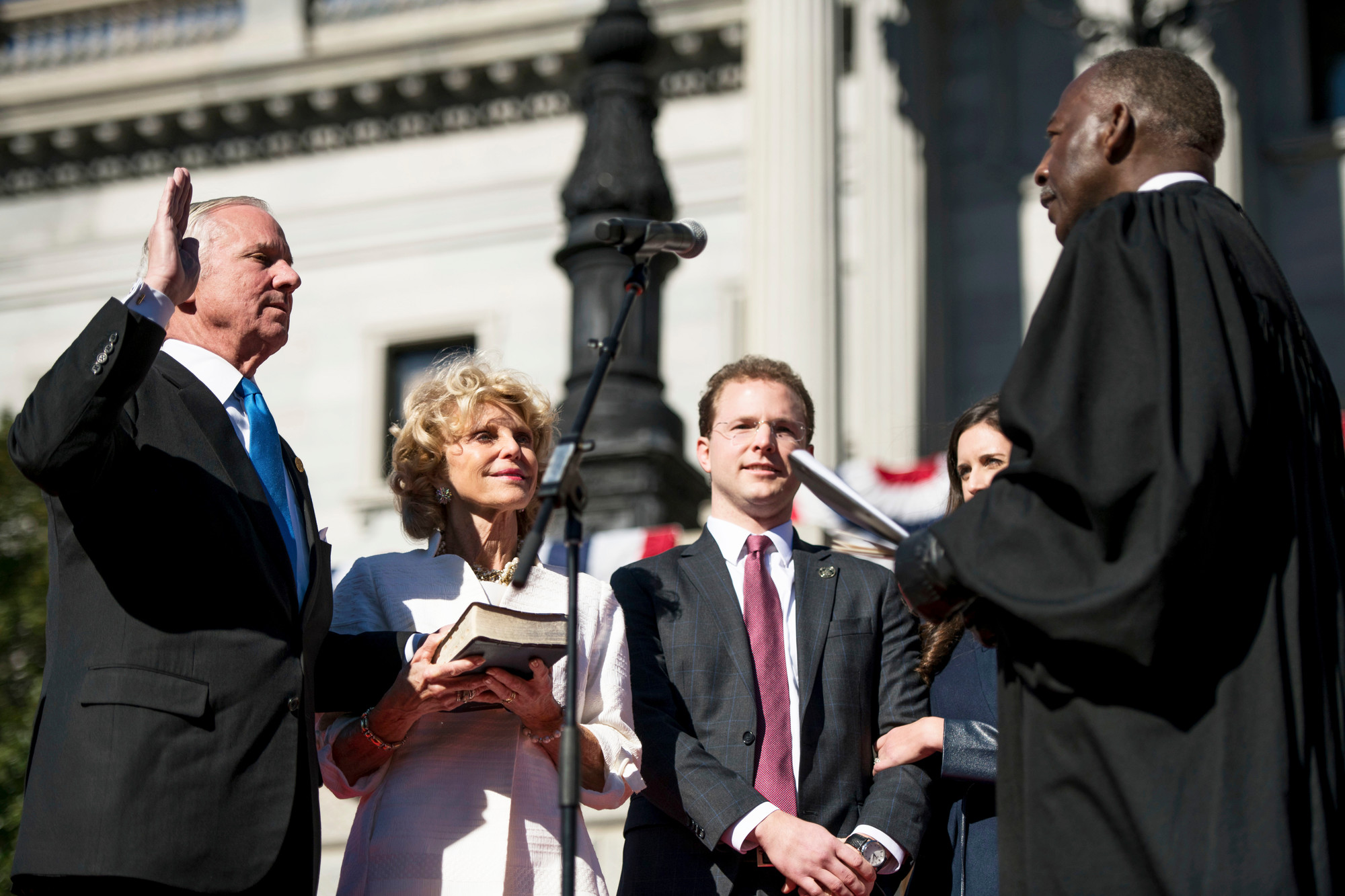 South Carolina Gov. Henry McMaster, left, takes the Oath of Office with Chief Justice Donald Beatty, right, outside the South Carolina Statehouse on Wednesday.  McMaster was joined by family including Peggy McMaster, second from left, and son Henry McMaster Jr.