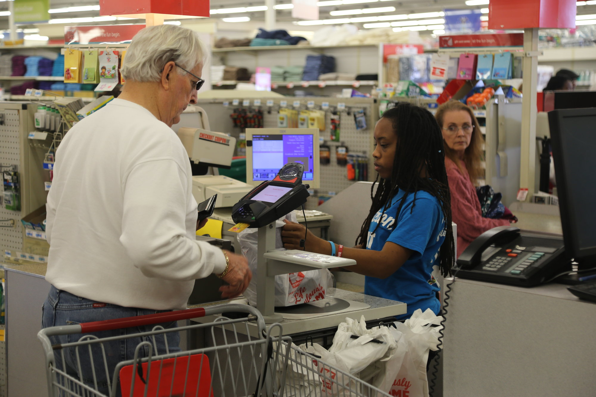 SUMTER ITEM FILE PHOTO A Sumter Kmart employee helps a customer at check-out recently.