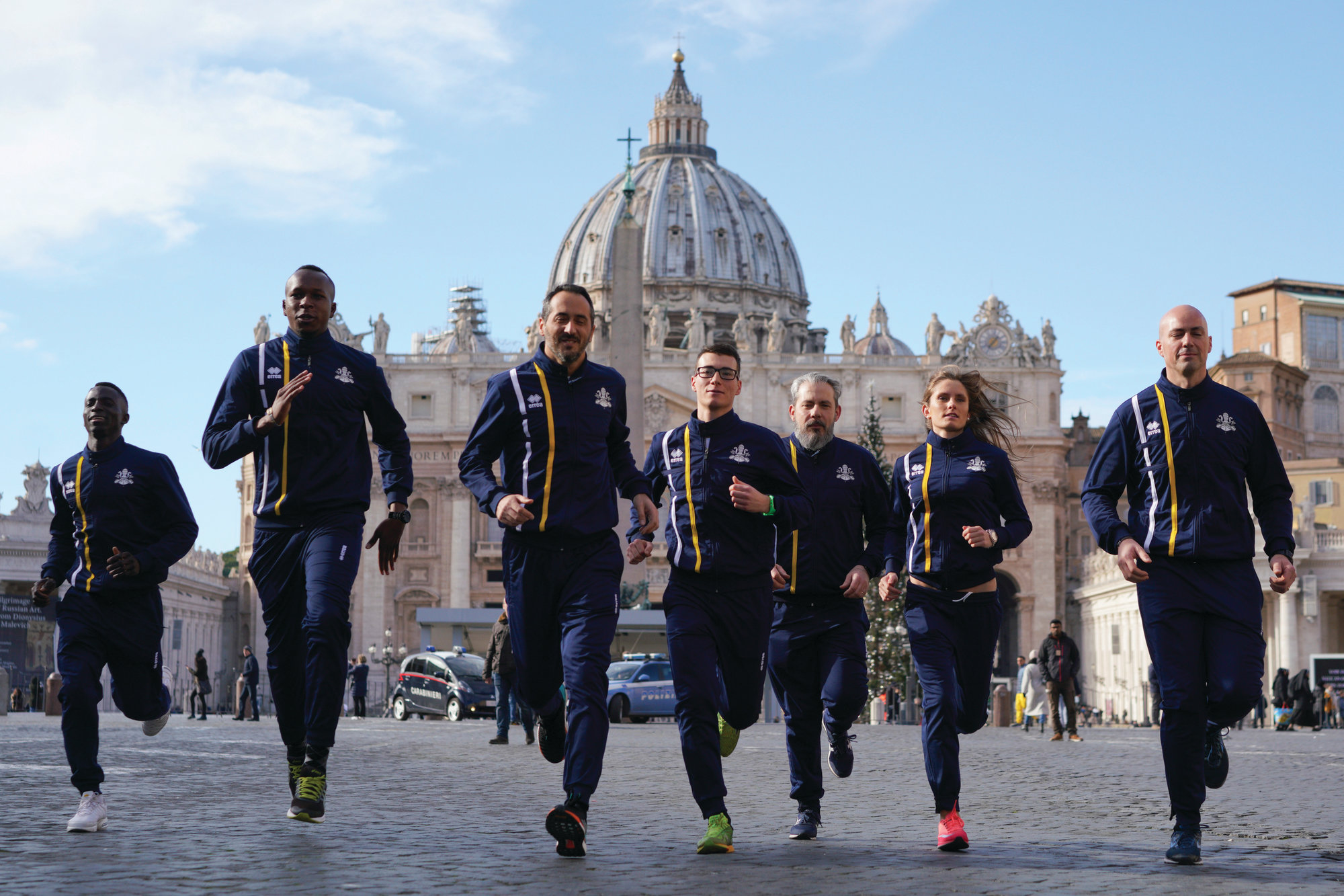 Athletes of the Athletic Vatican sports team run for the media in front of St. Peter's basilica on Thursday. About 60 Holy See employees are the first accredited members of Vatican Athletics.