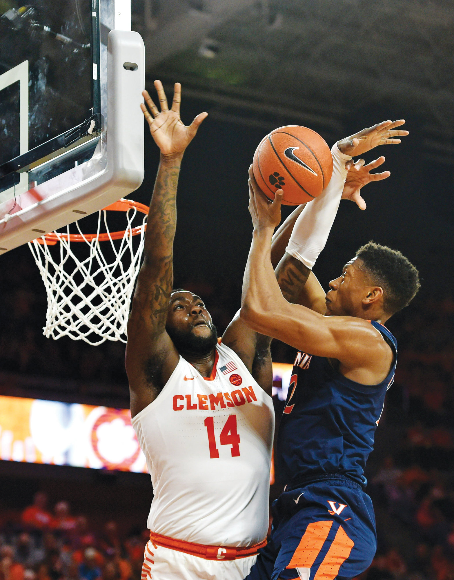 Virginia's DeAndre Hunter drives to the basket while defended by Clemson's Elijah Thomas during the first half of the Cavaliers' 63-43 victory over the Tigers on Saturday in Clemson.