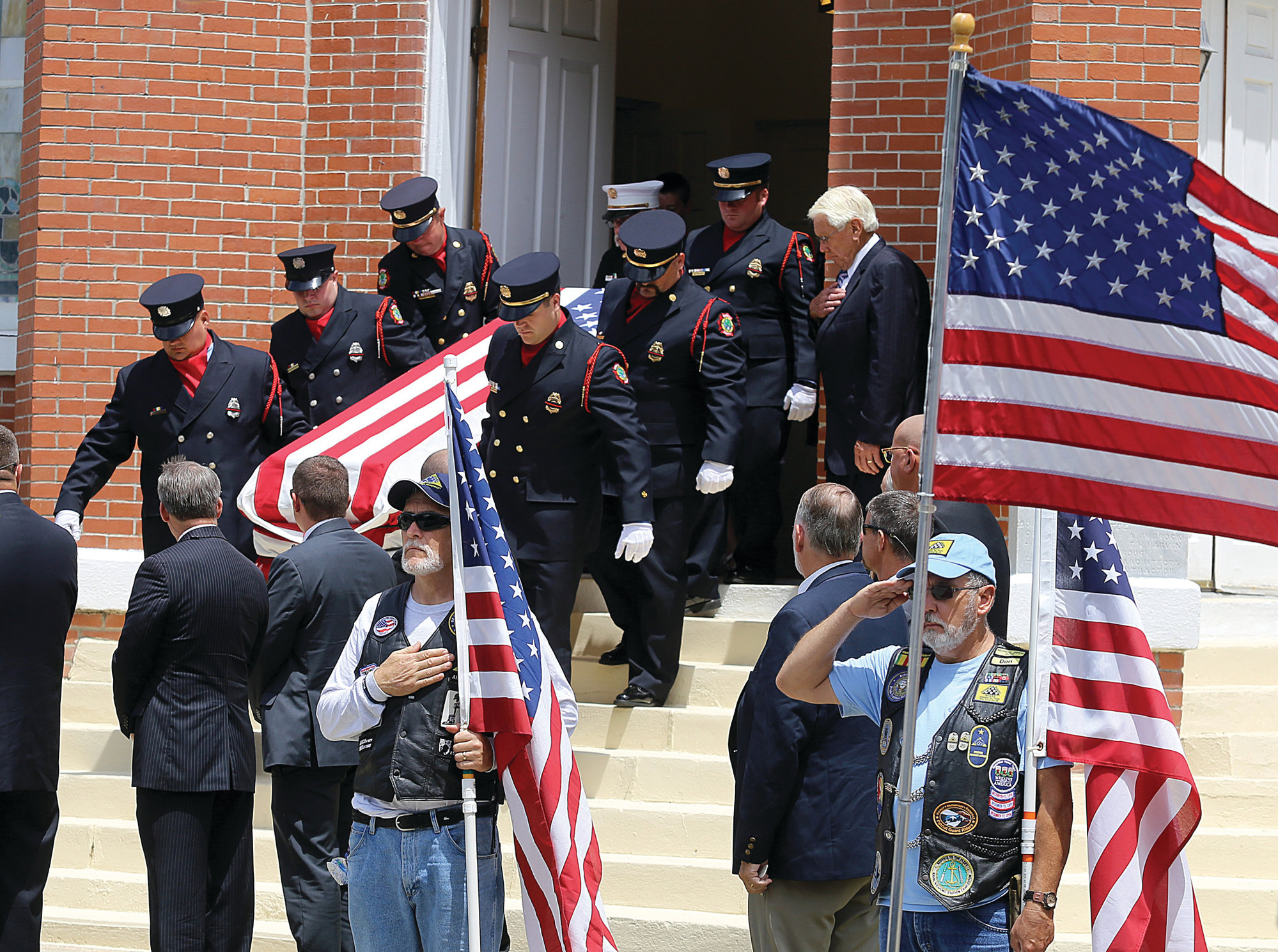SUMTER ITEM FILE PHOTO  Pallbearers carry the casket of Mason Moore out of the Summerton Baptist Church as members of the Patriot Guard Riders salute the fallen officer on May 28, 2017.