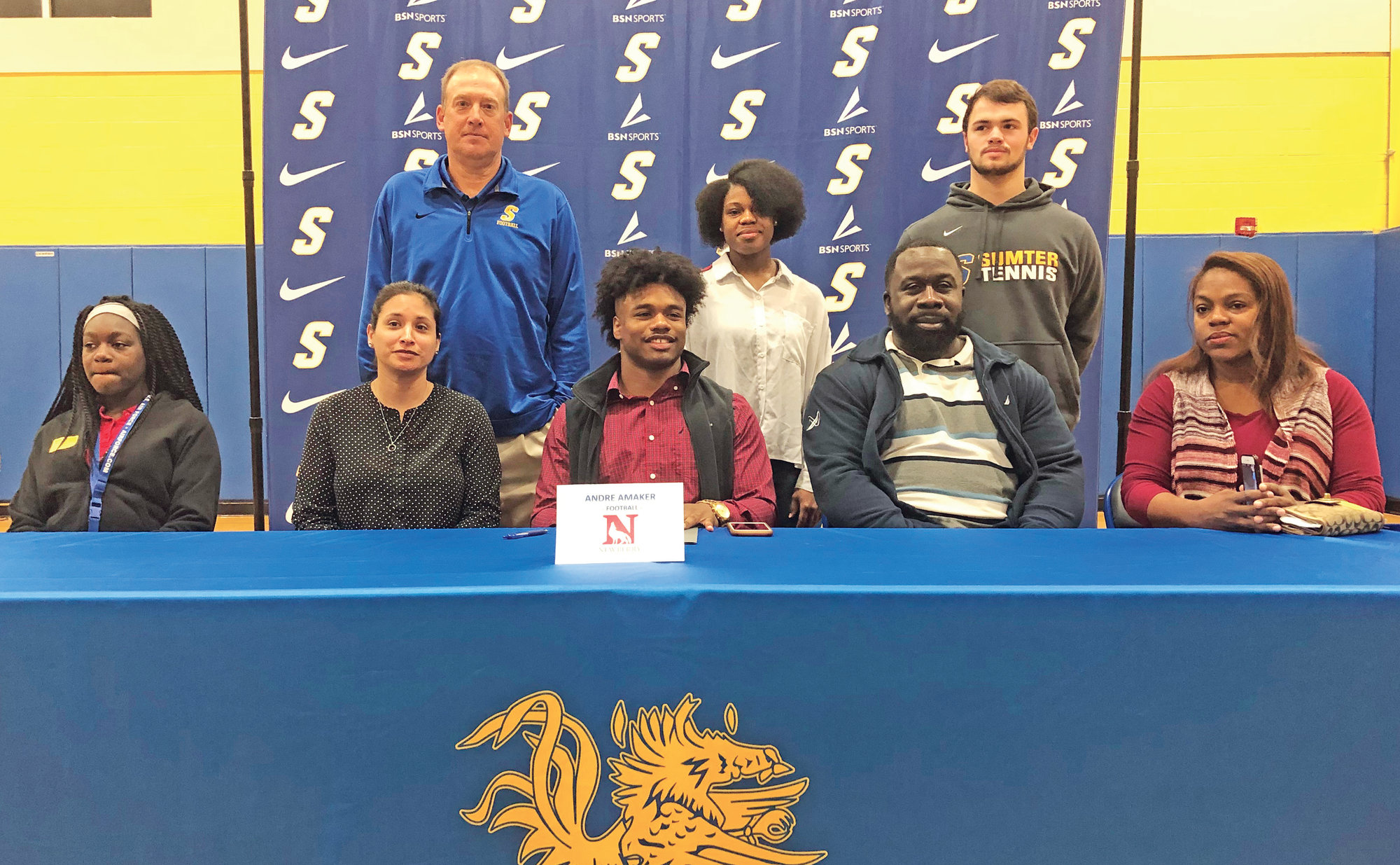 Sumter's Andre Amaker, middle, is flanked by family, best friend and coaches as he signs to play college football at Newberry College during a National Signing Day event at Sumter High on Wednesday.