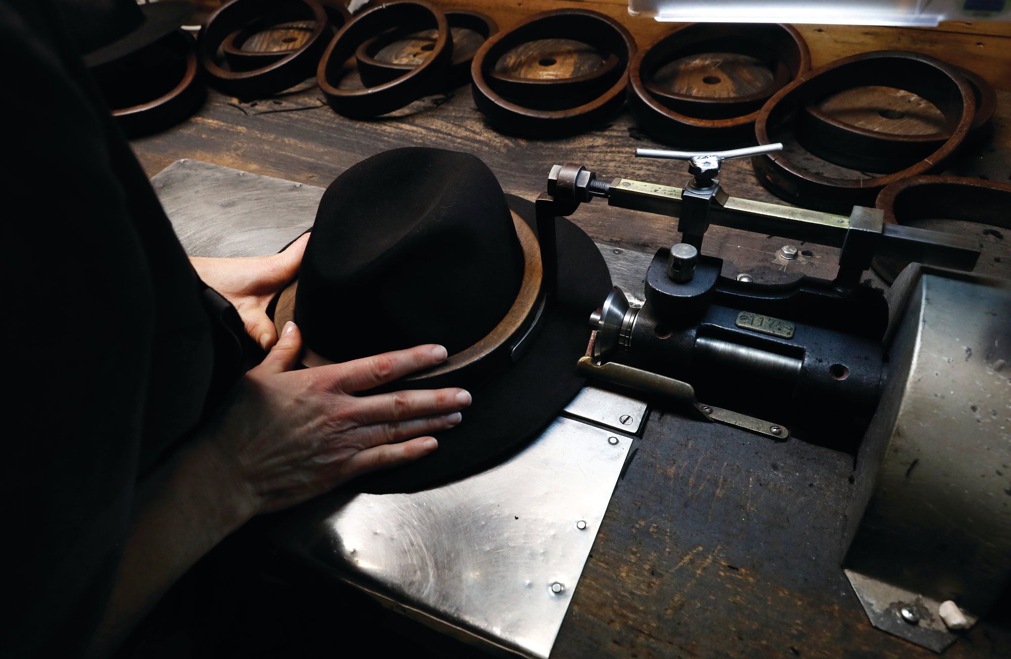 A man holds a hat inside the Borsalino hat factory. Borsalino's prized felt hats are handmade by 80 workers in its Piemonte factory.