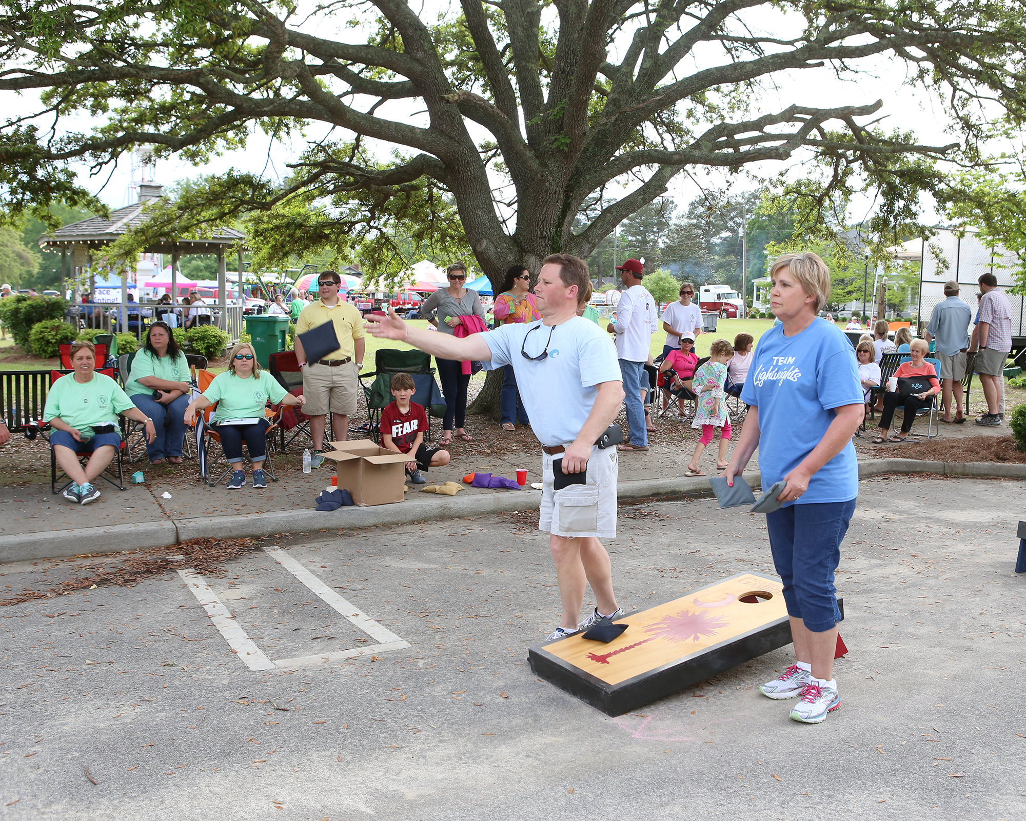 Ron Wingard and Katherine Turbeville play a game of corn hole as their friends and neighbors watch during the Puddin Swamp Festival on Saturday in Turbeville. (Keith Gedamke/The Item)