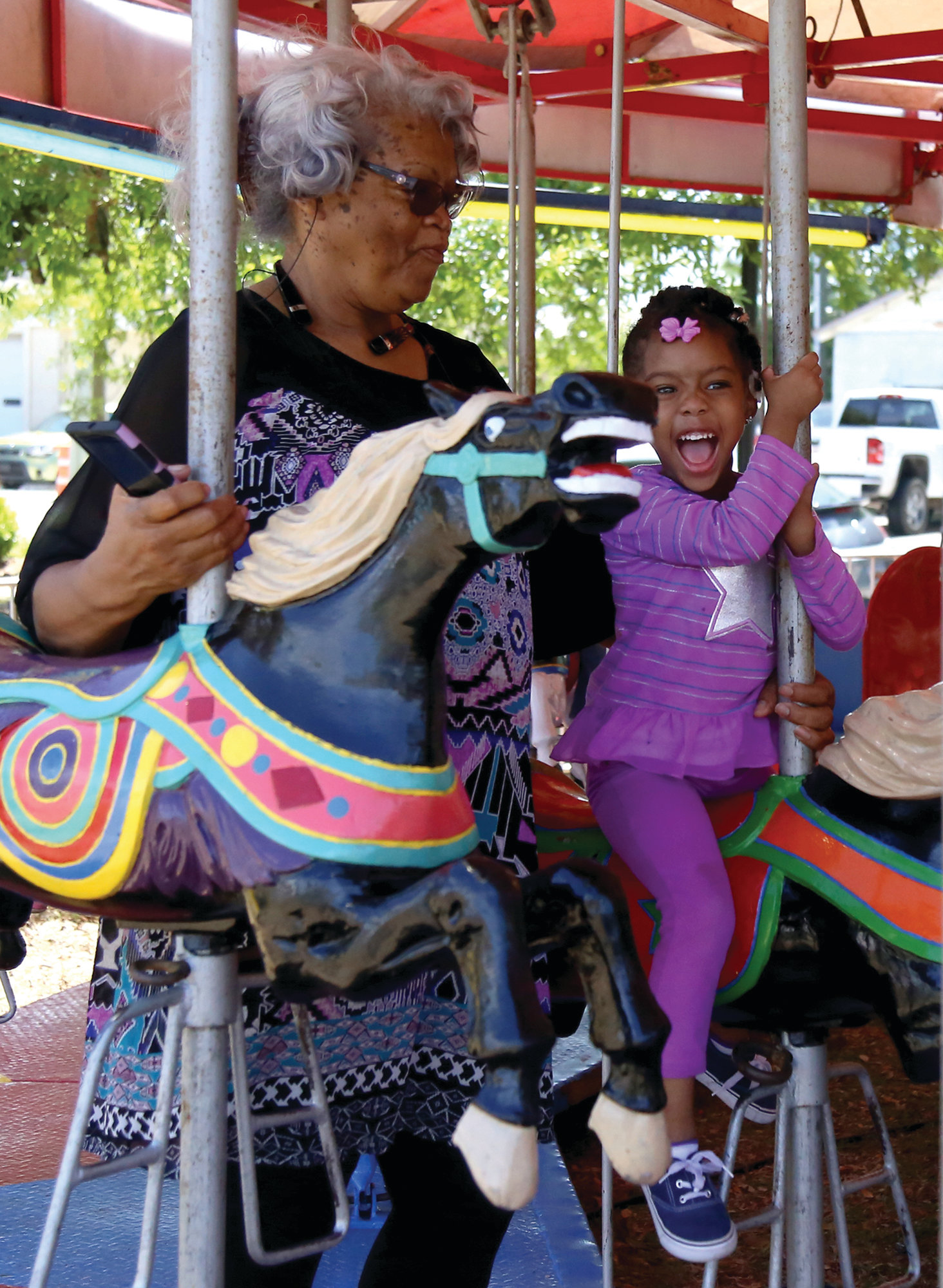 Virginia Lesane, looks on as her granddaughter, Chloe Lesane,4,laughs as she rides the carousel at the Puddin Swamp Festival on Saturday in Turbeville.