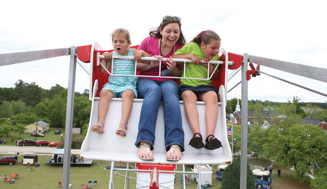 Millie Welch,3, Beth Horne, and Abby Welch,8, yell down to family while riding the ferris wheel at the Puddin Swamp Festival on Saturday. (Keith Gedamke/The Item)