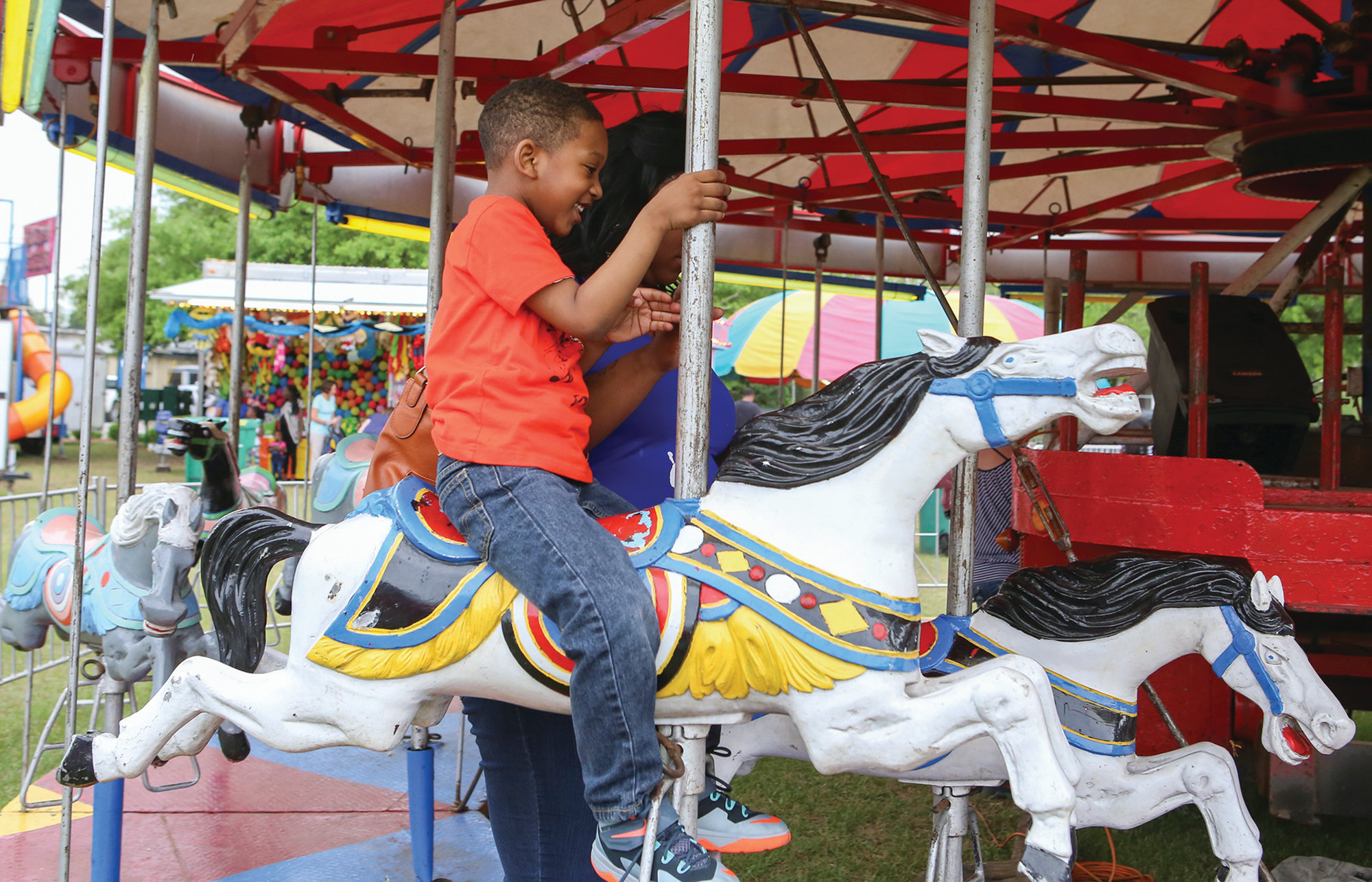 Gavriel Lasane,4, rides the Merry Go Round during the Puddin Swamp Festival on Saturday. (Keith Gedamke/The Item)
