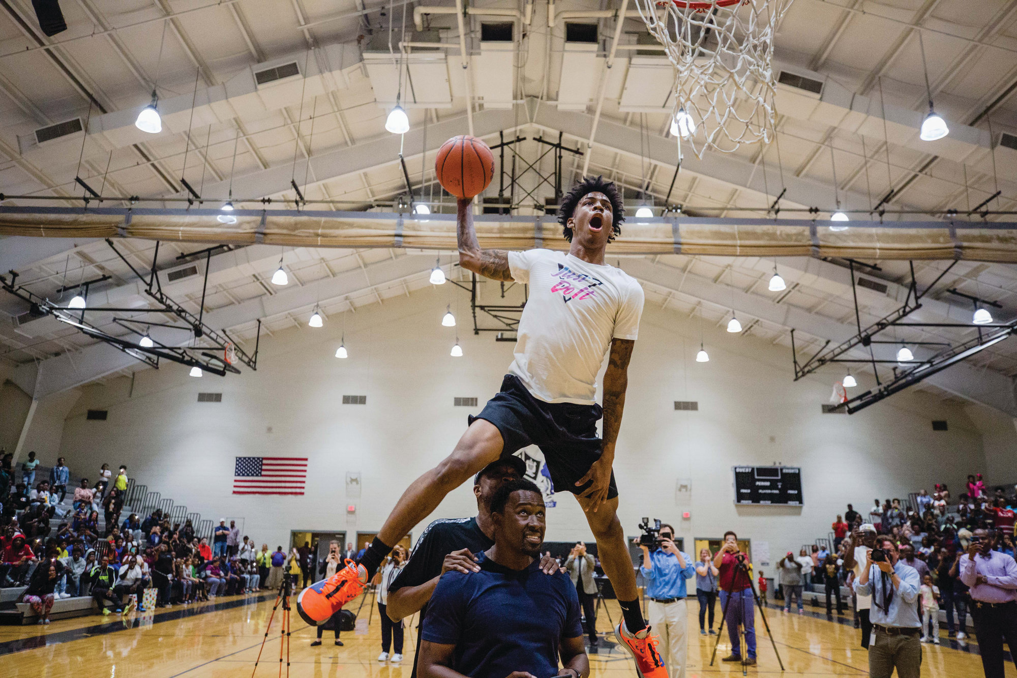 Ja Morant jumps over his father and uncle, Ronnie Morant and Phil Morant, on the way to a dunk on Monday.