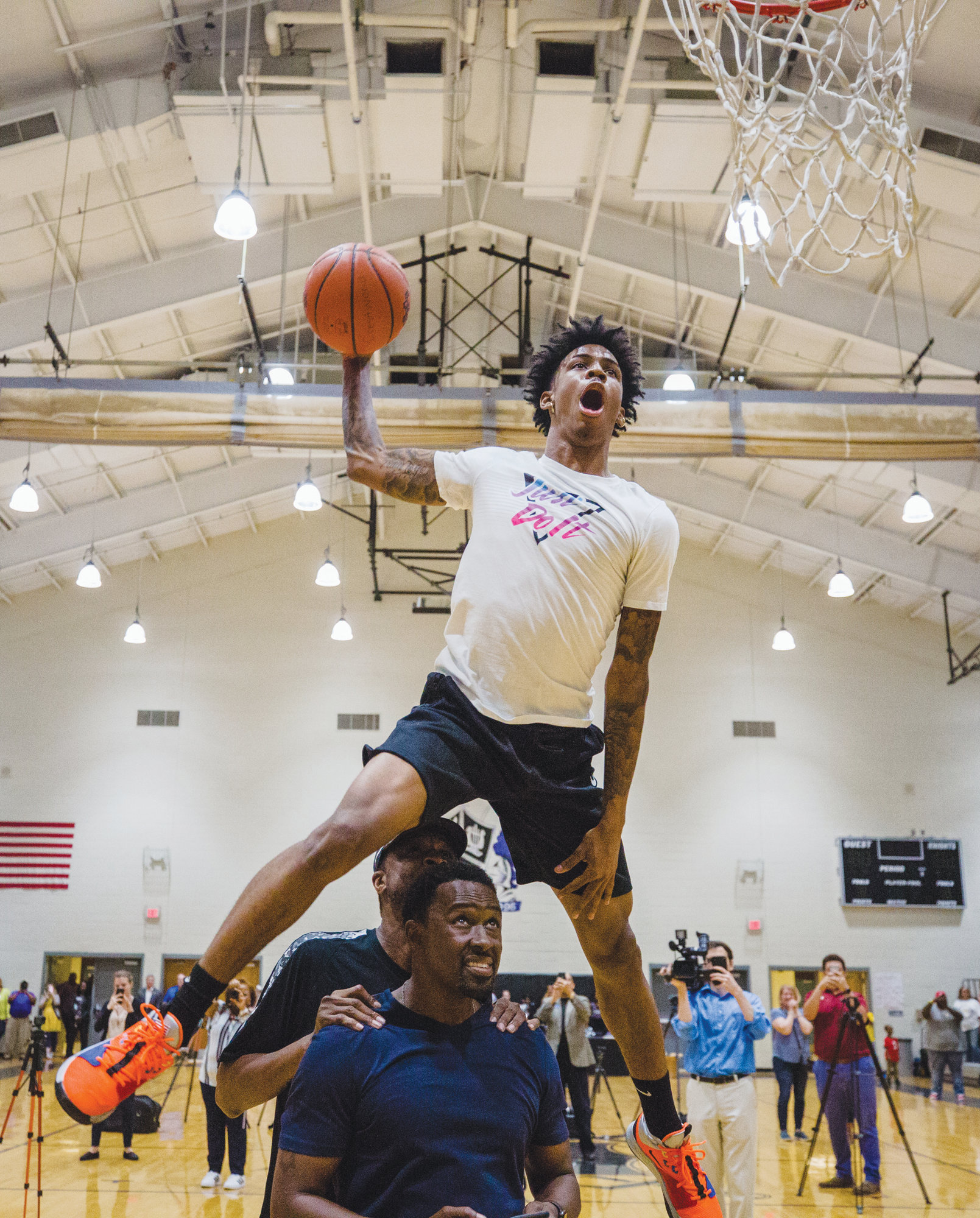 Former Crestwood standout Ja Morant goes over the top of two volunteers during a dunk demonstration on Monday at the Ja Morant Day celebration at Crestwood High School.