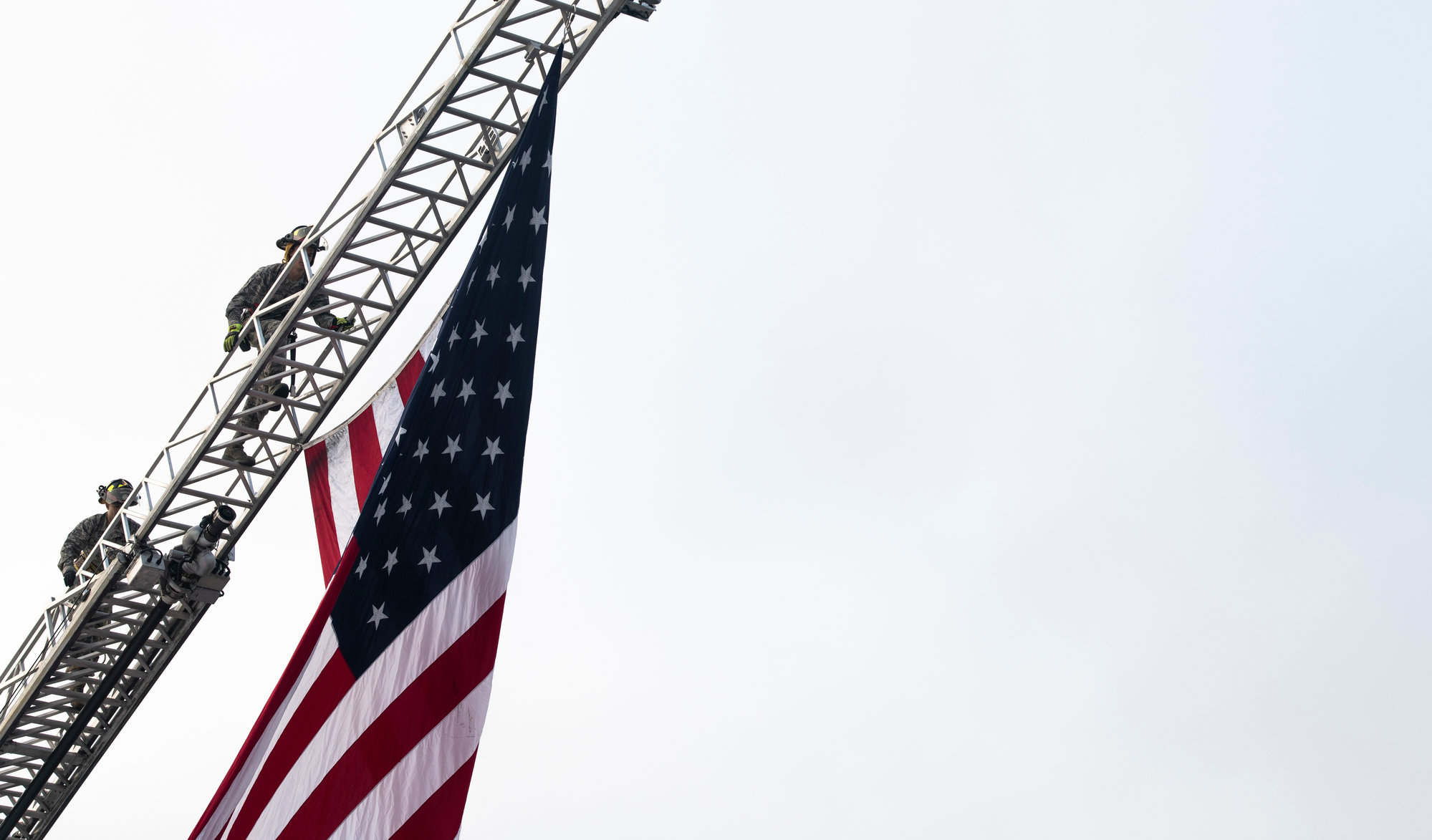 U.S. airmen assigned to the 20th Civil Engineer Squadron fire department climb a ladder after raising a flag prior to a flightline 5K at Shaw Air Force Base on Saturday. Along with static displays, guests also received the opportunity to interact  with military and civilian members.