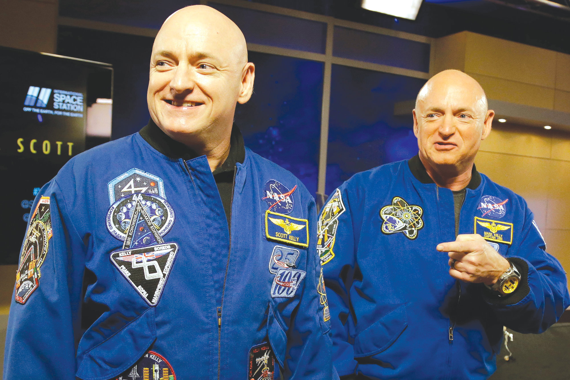 NASA astronaut Scott Kelly, left, and his identical twin, Mark, stand together before a news conference in Houston in 2016.
