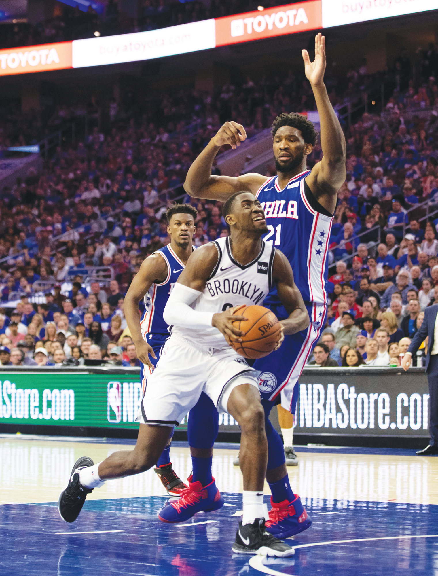 Brooklyn Nets' Caris LeVert, left, drives to the basket against Philadelphia 76ers' Joel Embiid, right, of Cameroon, during the second half in Game 1 of a first-round NBA basketball playoff series, Saturday, April 13, 2019, in Philadelphia.  The Nets won 111-102. (AP Photo/Chris Szagola)