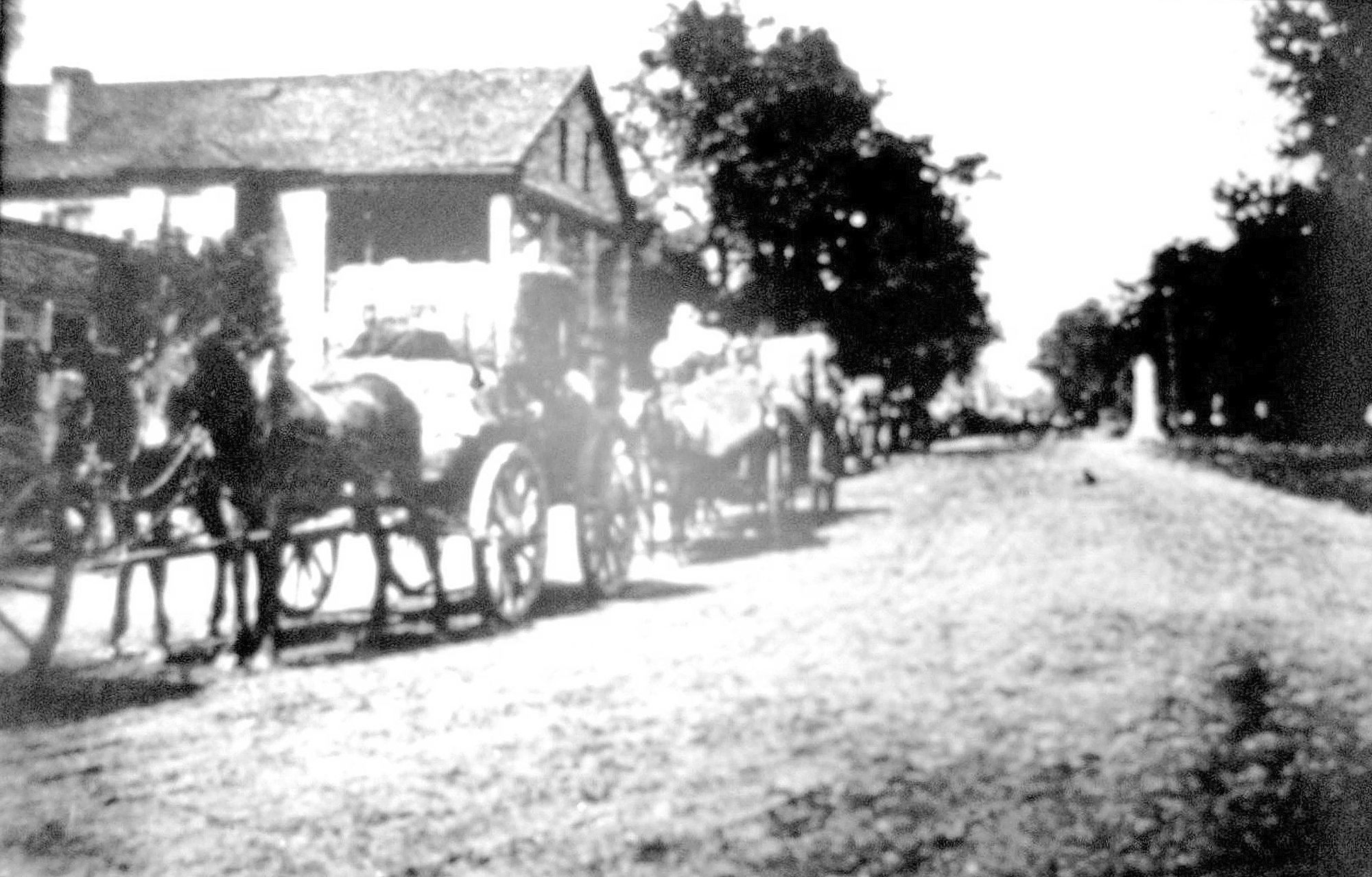 Cotton leaves the train platform passing in front of the Curtis House circa 1900.