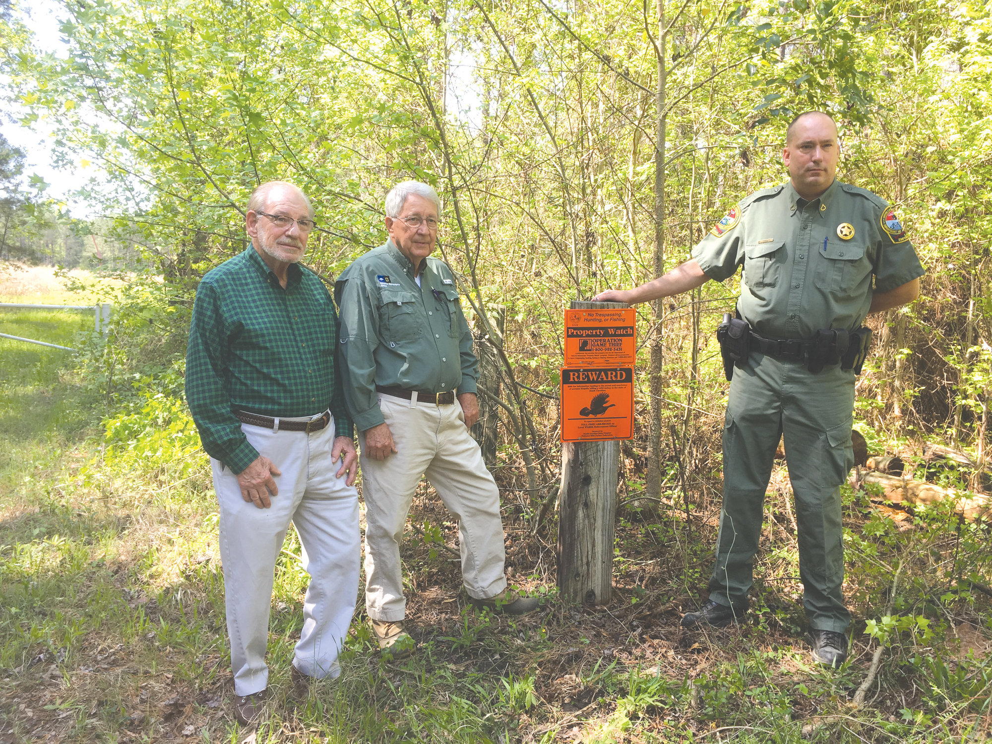 Landowners Marvin Davant, Hugh Ryan and SCDNR Officer Ed Laney are seen at the posted entrance to a rural property.