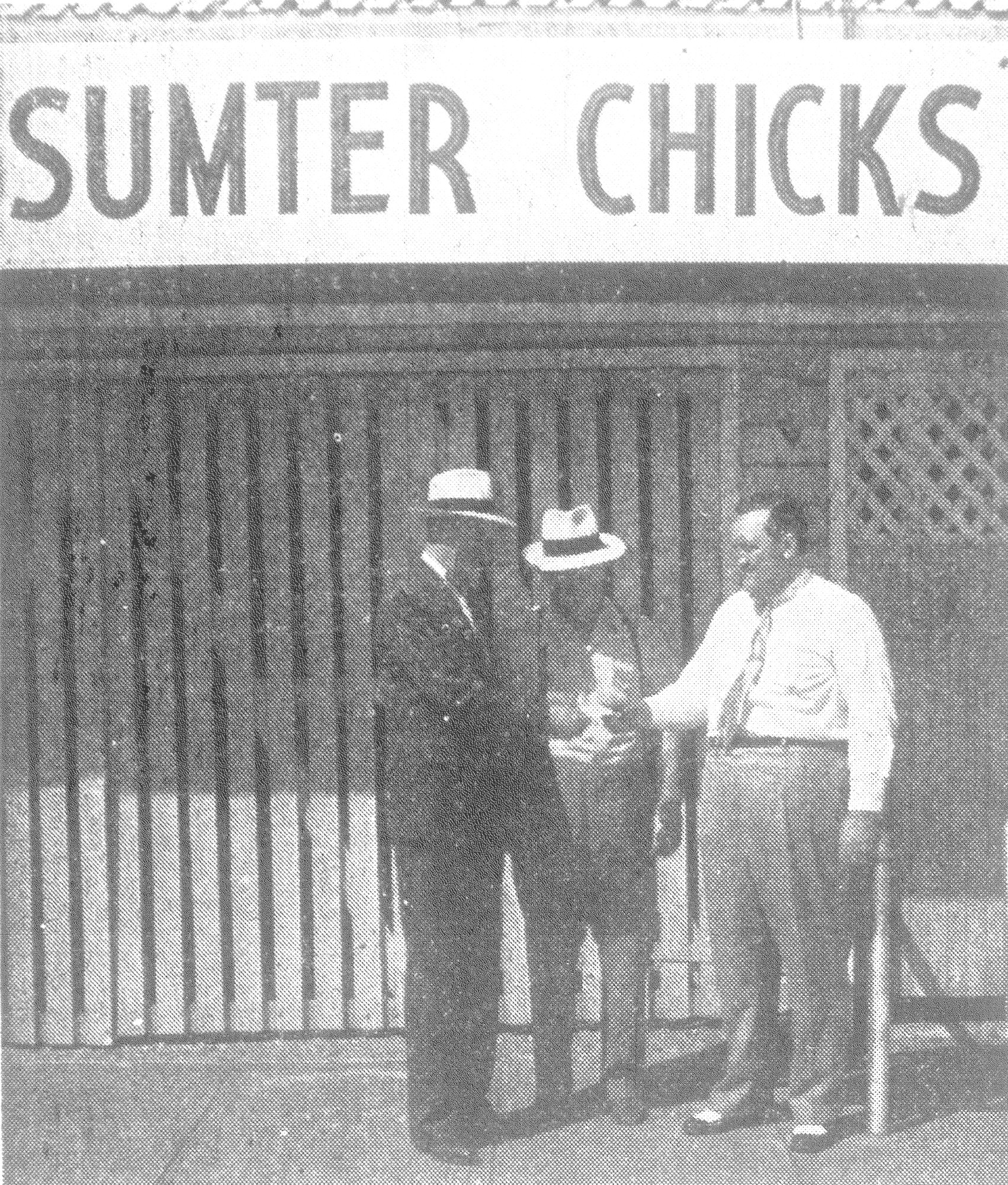 1950 - Mayor W. E. Bynum buys the first ticket for the Chicks' four-game series with Asheville and three-game series with Knoxville during Baseball Week in Sumter, June 19-25, from A. T. Heath Jr., president, Sumter Chicks Inc., while Troy Agnew, center, the club's general manager, looks on. The advance sale was designed to increase attendance at Riley Park and ensure the continuance of Tri-State League baseball in Sumter.